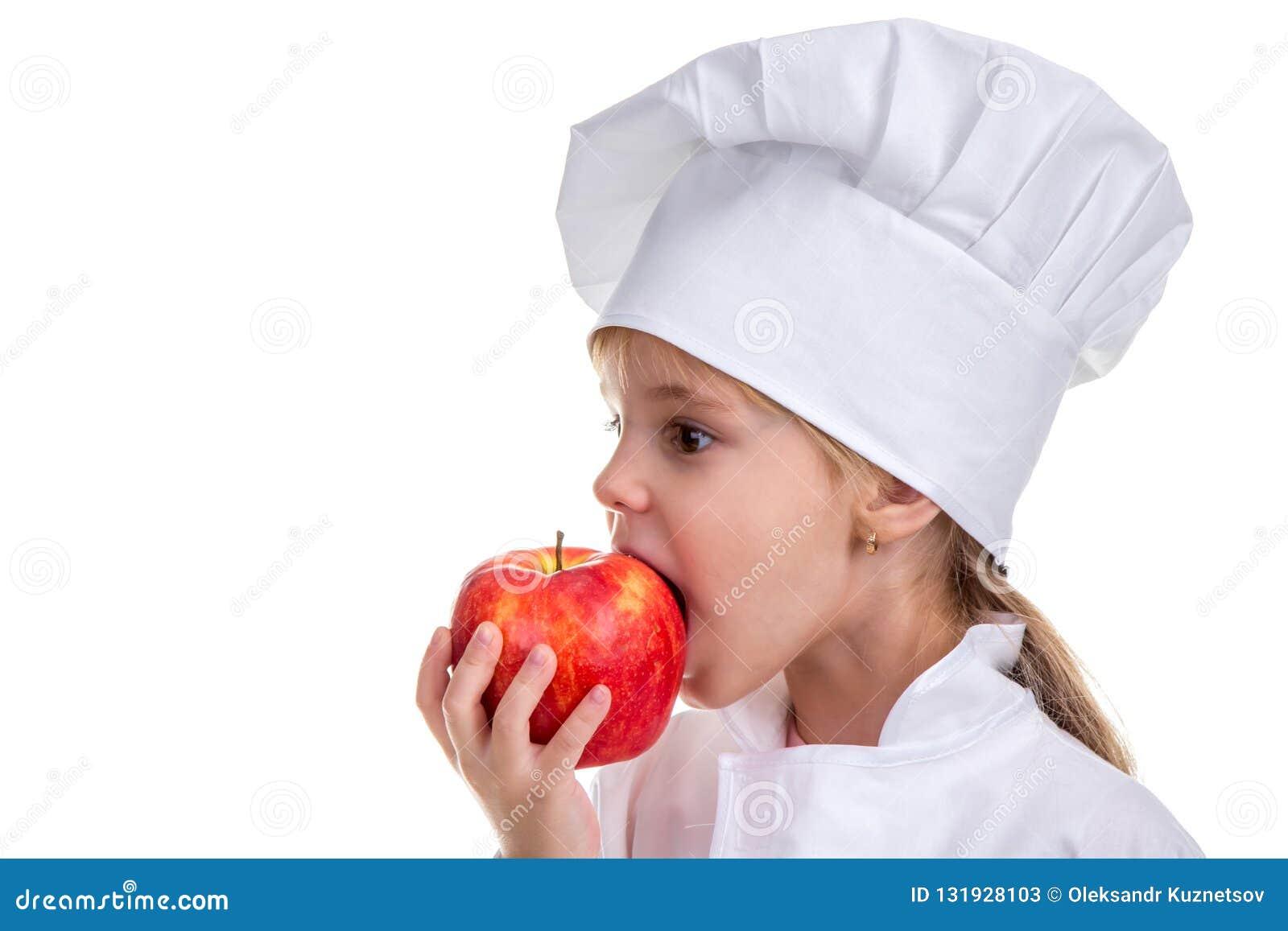 Bambina in un cappuccio del cuoco che morde la mela rossa Concetto di alimento sano e dello stile di vita sano Immagine di profil