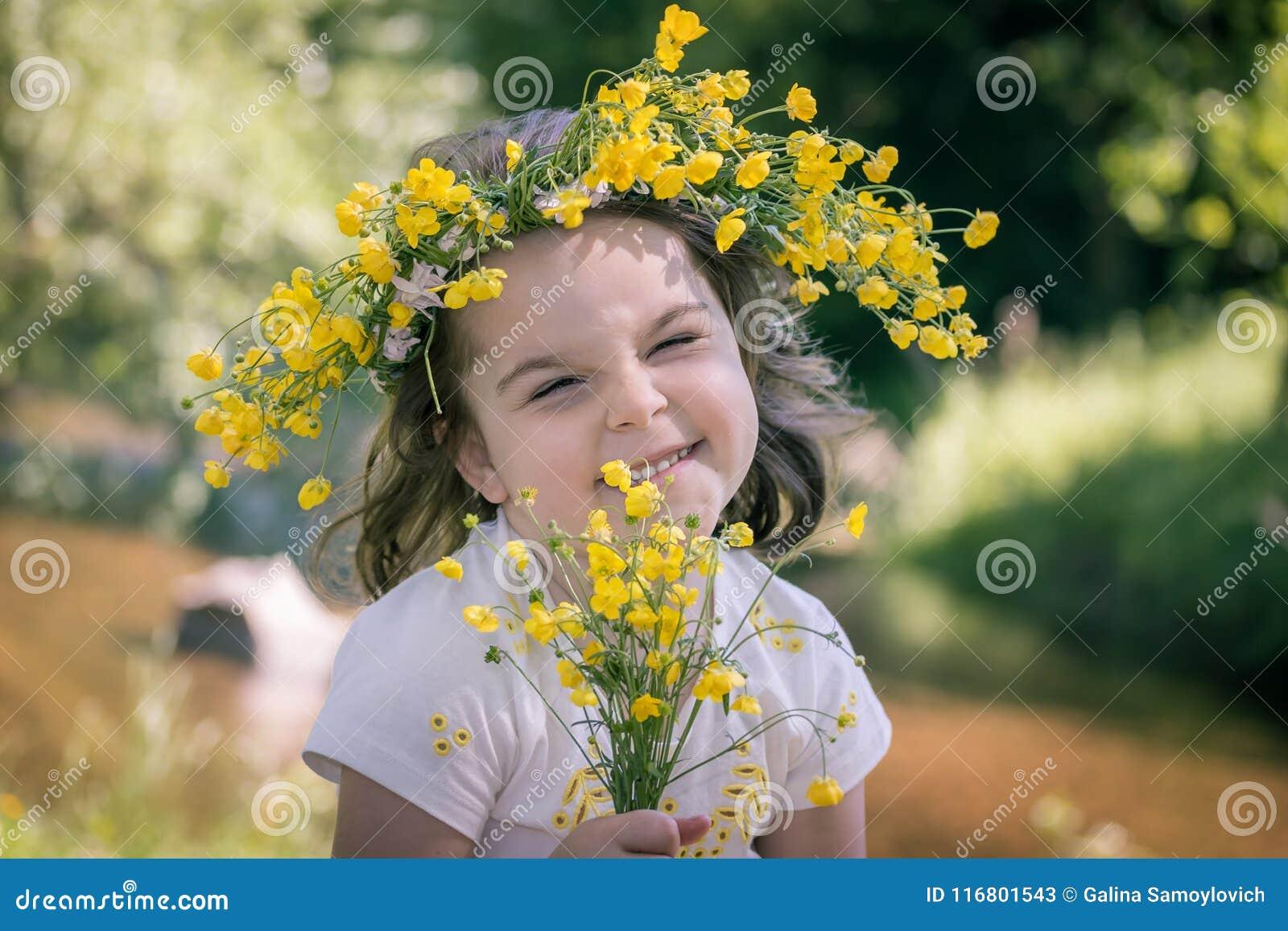 Bambina in una corona dei fiori gialli