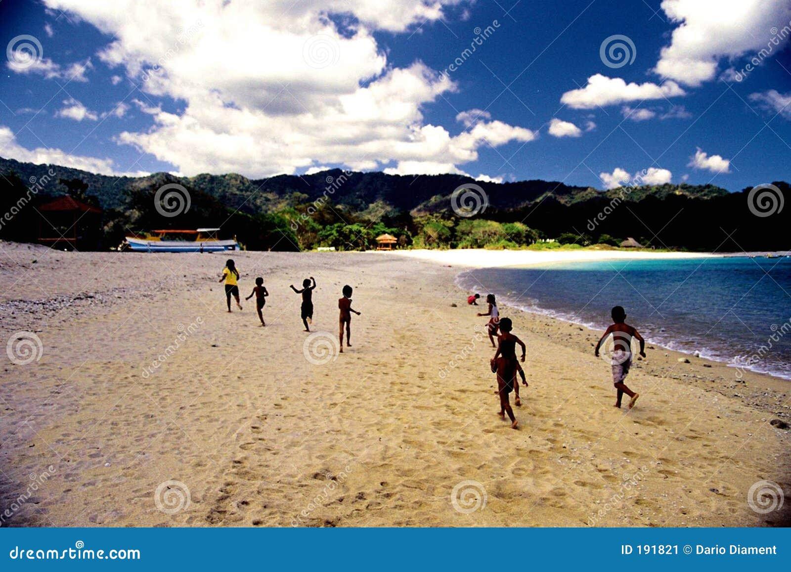 Bambini che funzionano sulla spiaggia