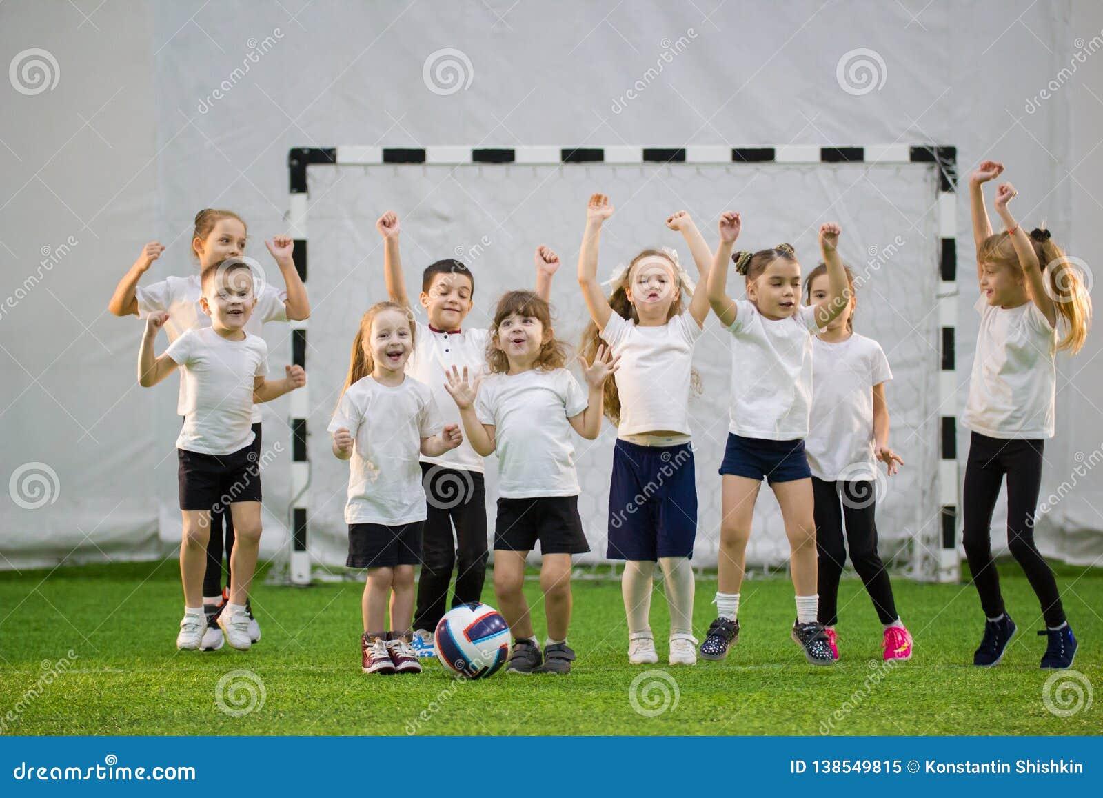 Bambini che giocano a calcio all interno Squadra di football americano dei bambini Mani su e saltare
