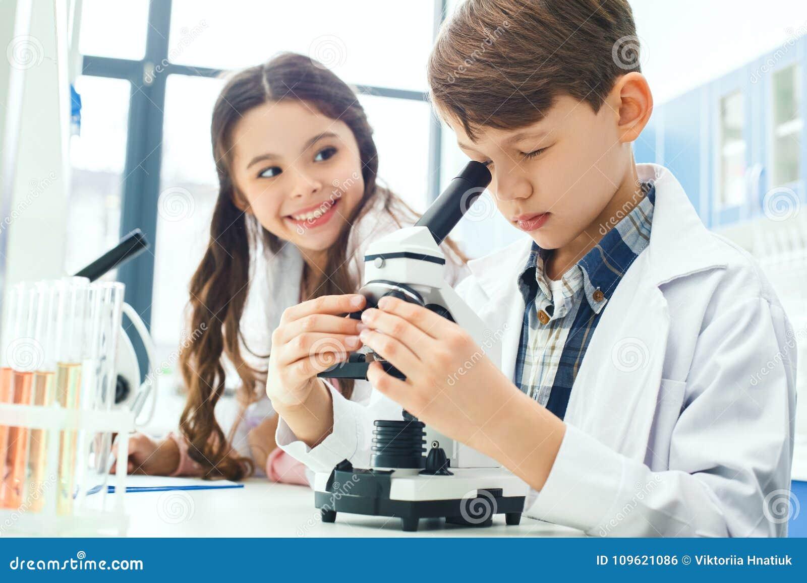Bambini che imparano chimica nelle note di esperimento del microscopio del laboratorio della scuola