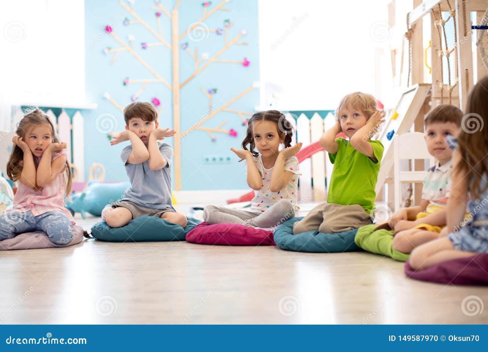 Bambini che mettono sul pavimento e gesti di manifestazione che fanno compito