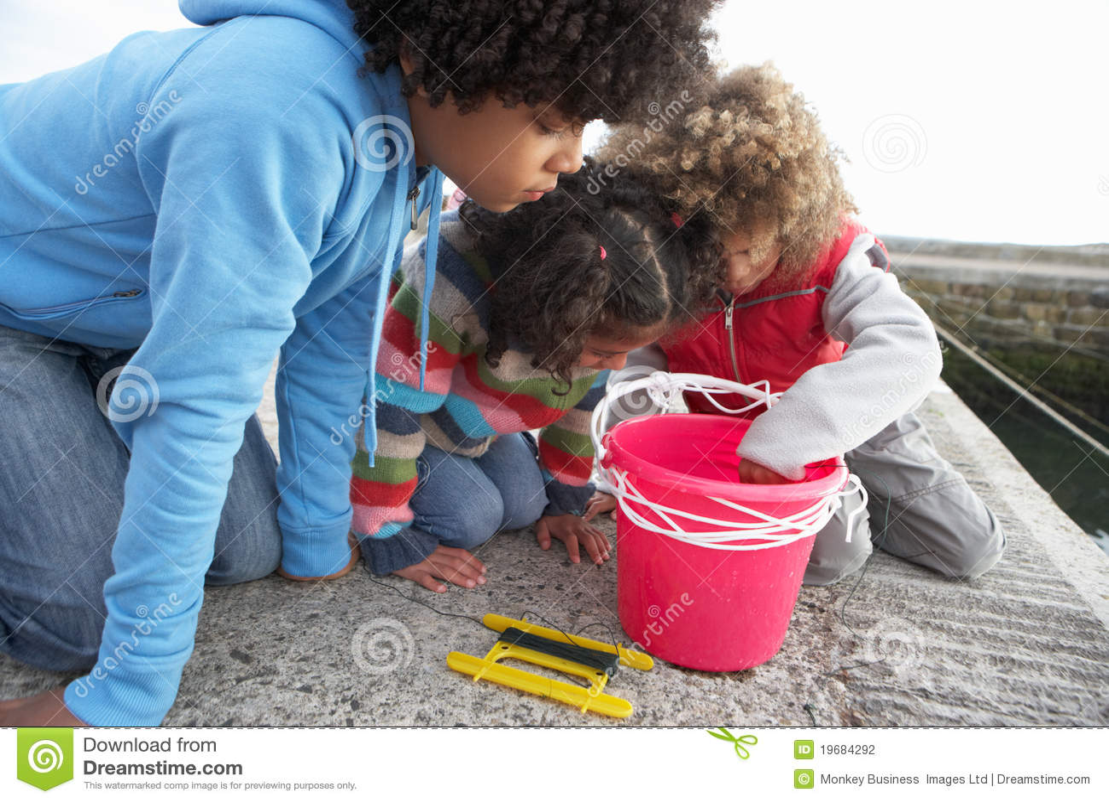 Bambini che pescano per i granchi