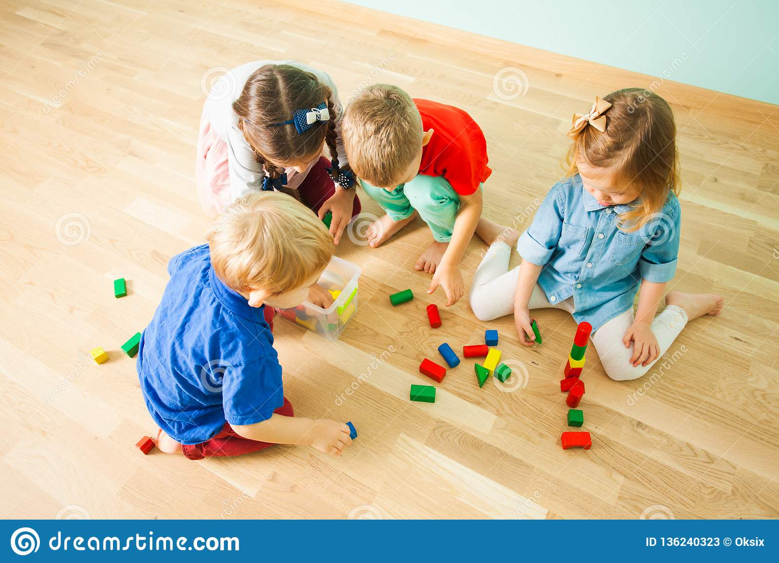 Bambini che raccolgono i giocattoli dopo il gioco all asilo