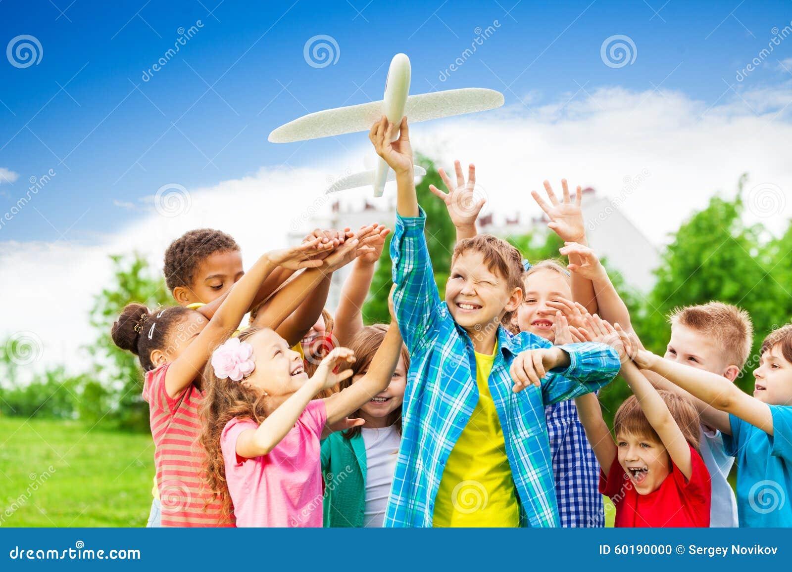 Bambini che raggiungono dopo il grande giocattolo bianco dell aeroplano