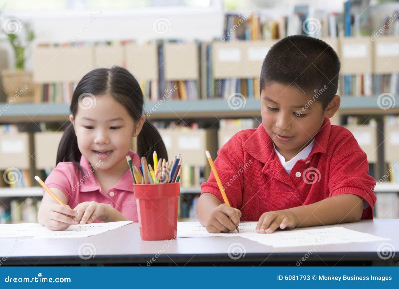 Bambini che si siedono allo scrittorio e che scrivono nell 39 aula immagine stock immagine di - Bambini che si guardano allo specchio ...