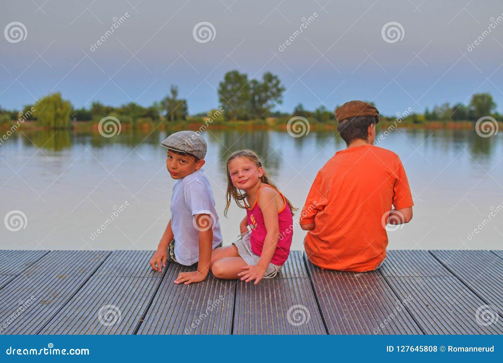 Bambini che si siedono sul pilastro siblings Tre bambini dell età differente - ragazzo dell adolescente, ragazzo elementare di et