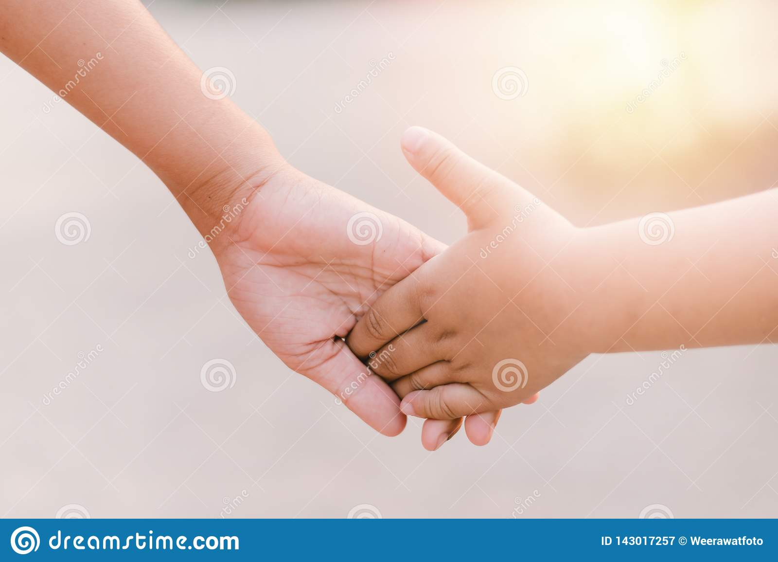 Bambini che si tengono per mano mentre camminando al tramonto