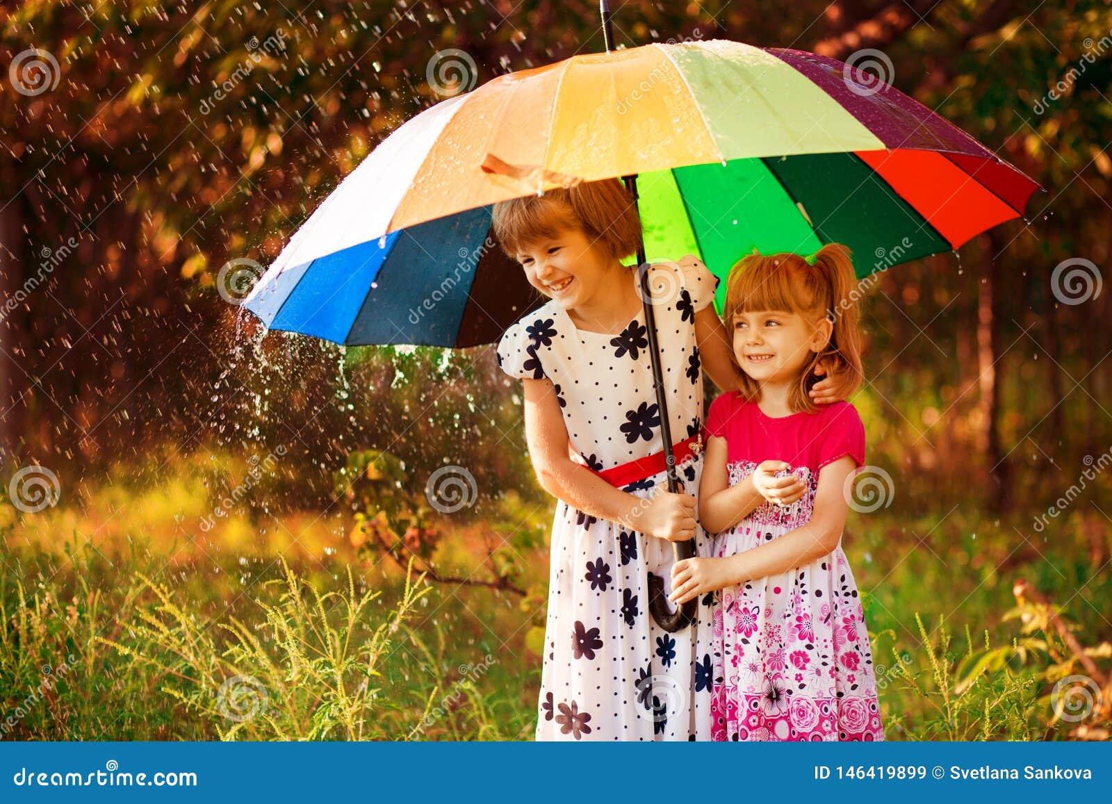 Bambini con l ombrello variopinto che gioca in pioggia della doccia di autunno Le bambine giocano in parco da tempo piovoso