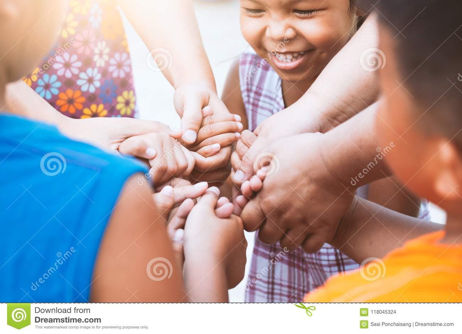 Bambini e genitore che si tengono per mano insieme e che giocano