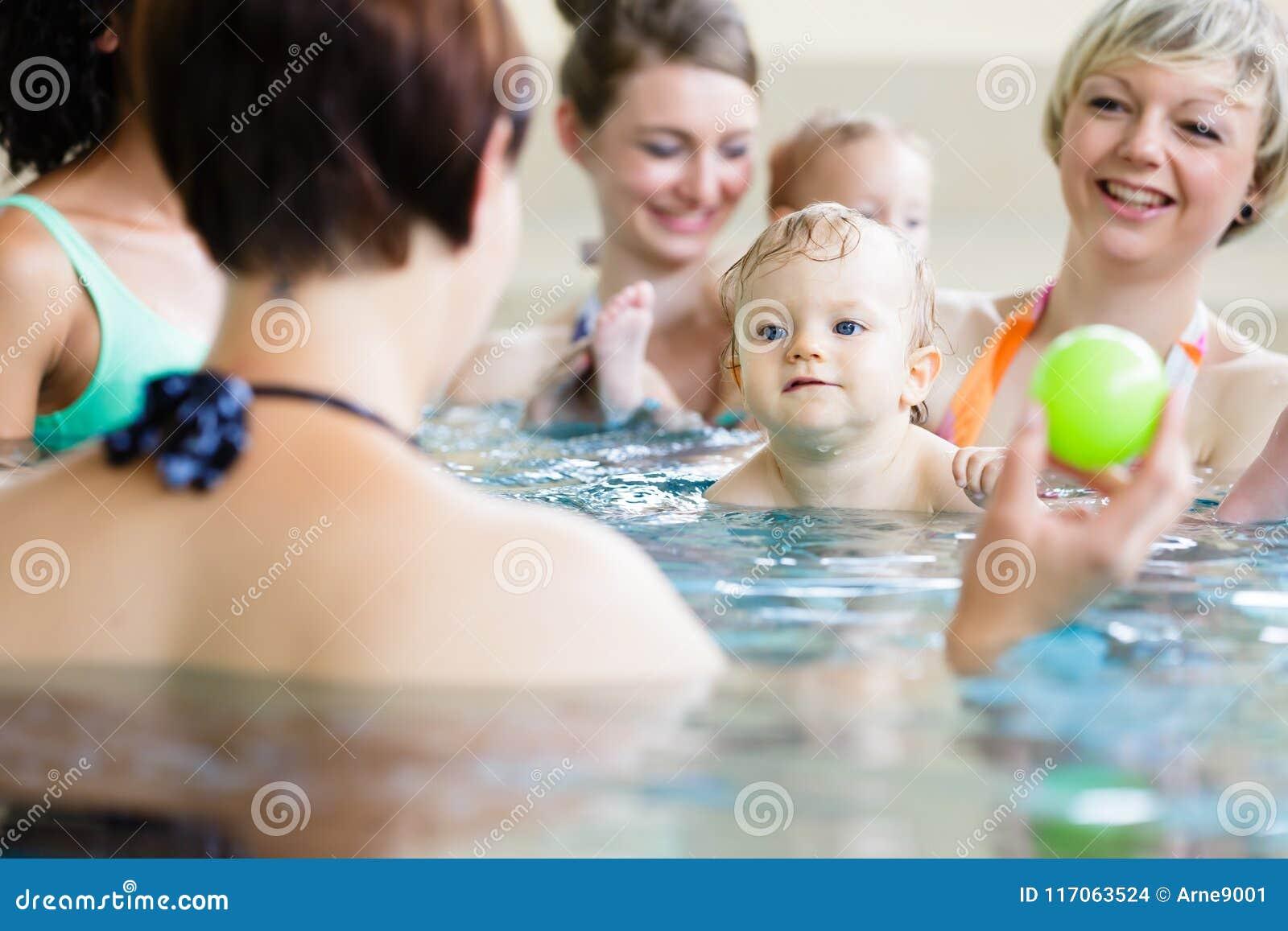 Bambini e le loro mamme alla classe di madre-e-bambino-nuoto