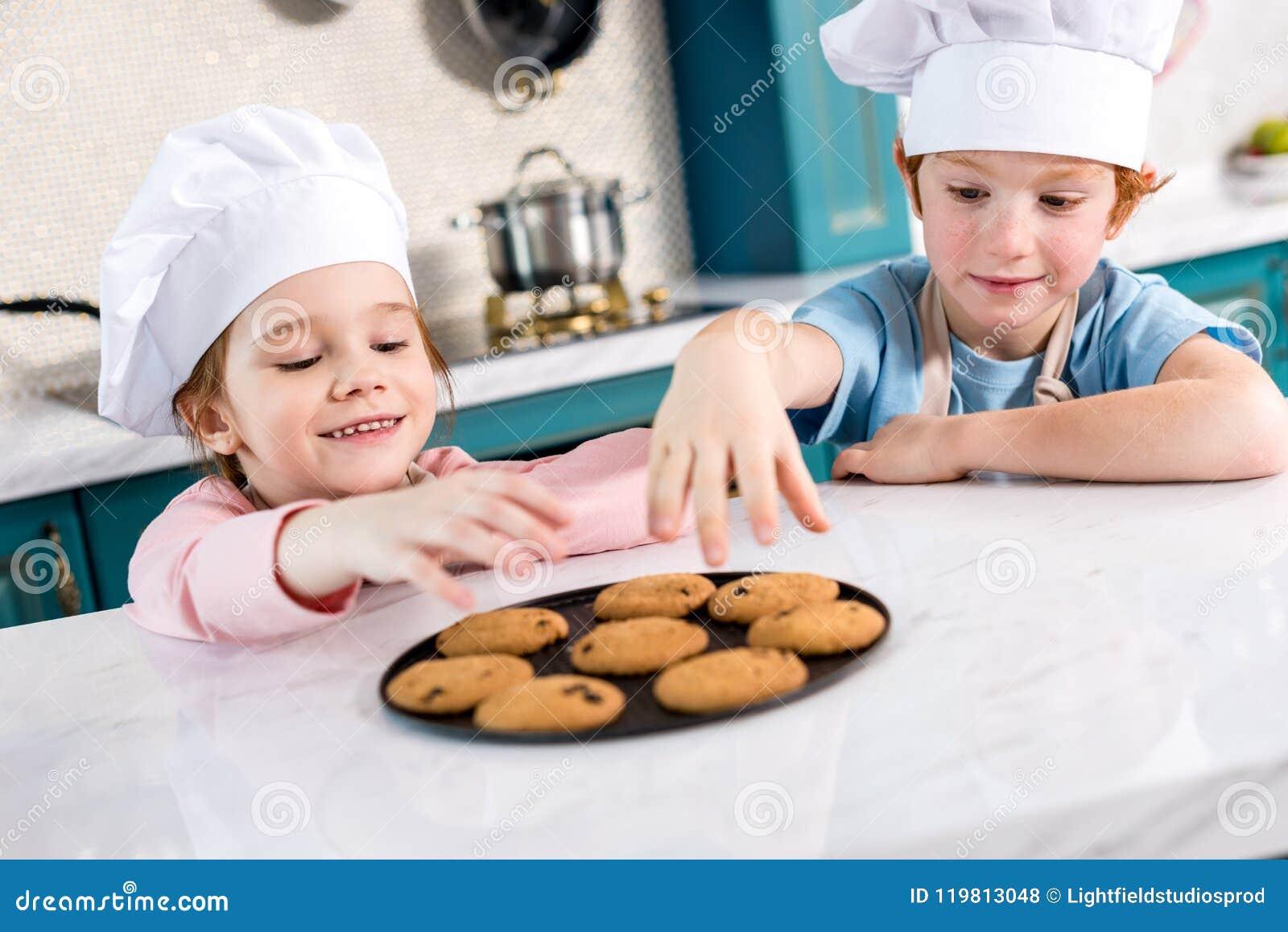 Bambini felici in cappelli del cuoco unico che mangiano i biscotti saporiti