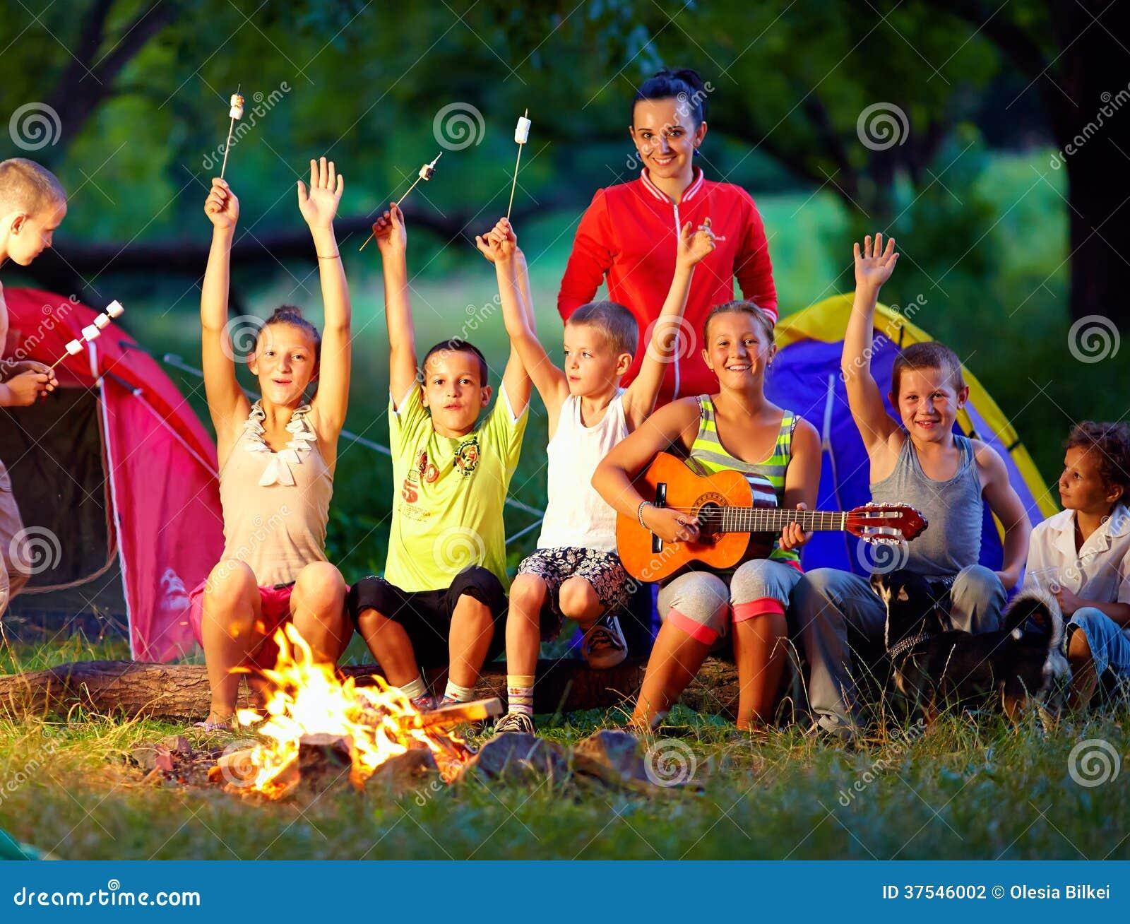 Bambini felici che cantano le canzoni intorno al fuoco del campo