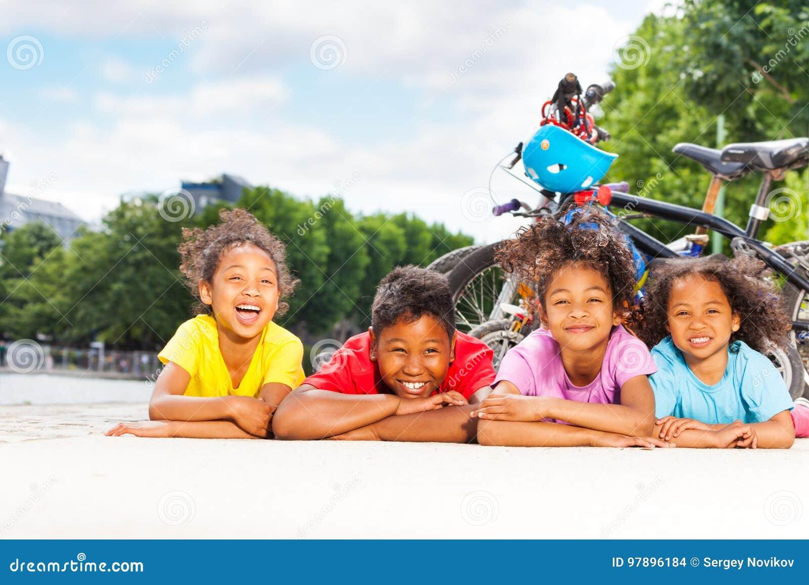 Bambini felici che riposano dopo il riciclaggio all aperto