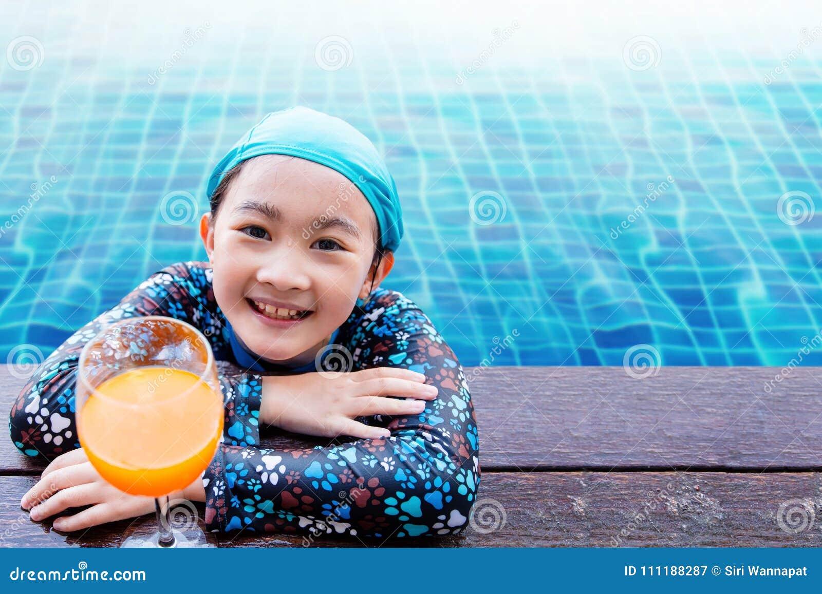 Bambini felici sul lato della piscina, ragazza che si rilassa con la somma