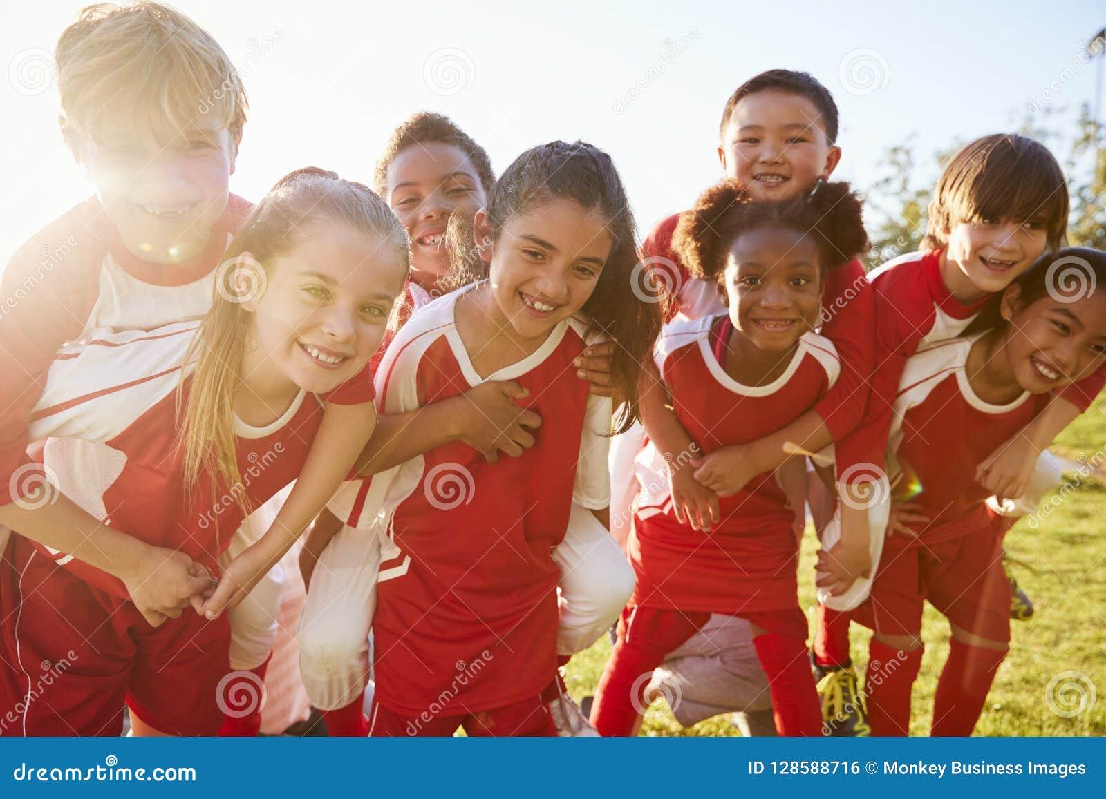 Bambini nel gruppo di sport della scuola elementare che trasporta sulle spalle all aperto