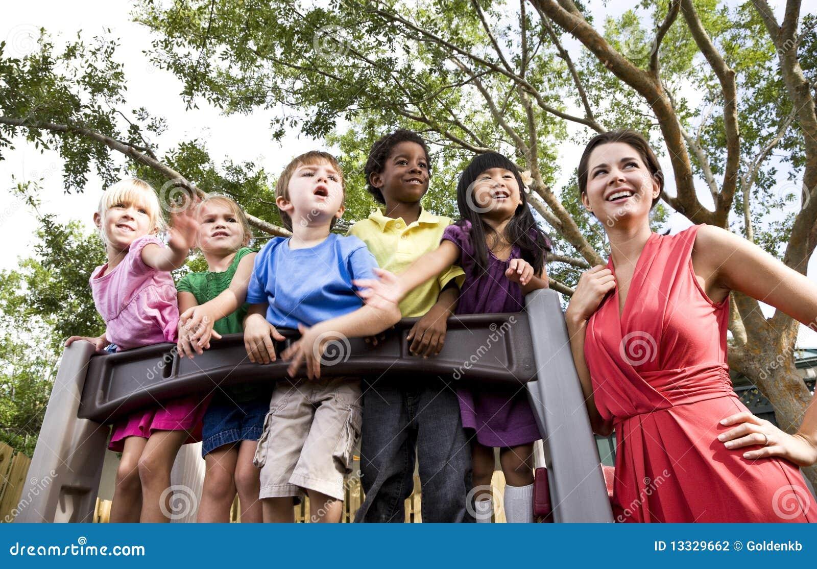 Bambini prescolari sul campo da giuoco con l insegnante