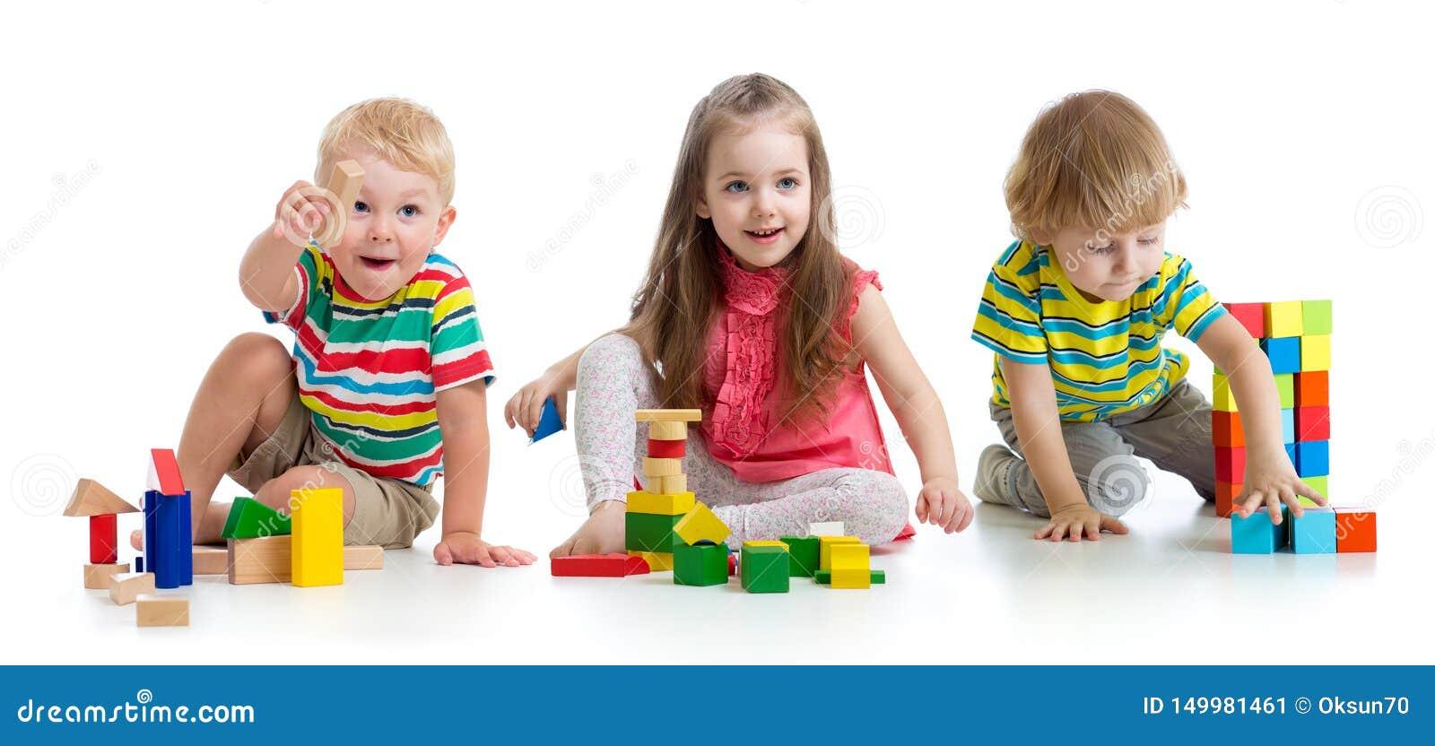 Bambini svegli che giocano con i giocattoli o i blocchi e che si divertono mentre sedendosi sul pavimento isolato sopra fondo bia