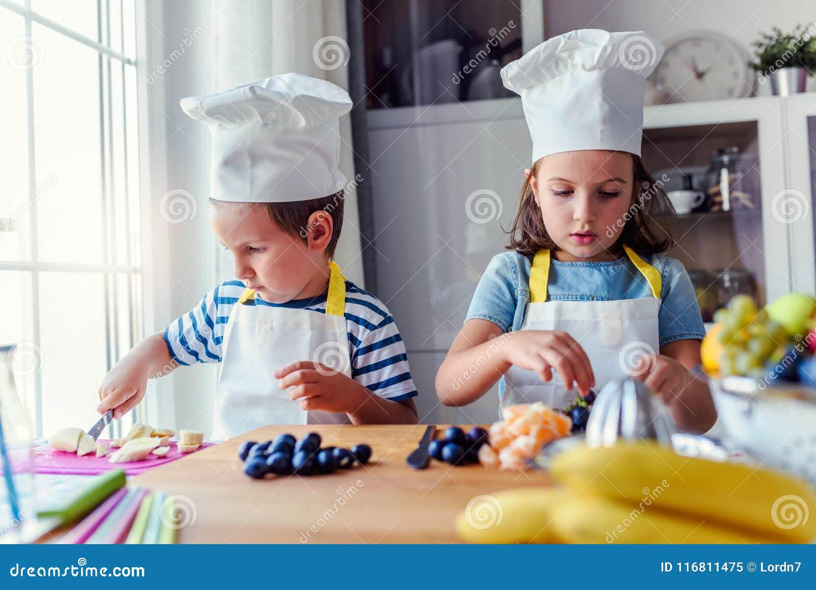 Bambini svegli che preparano una macedonia in cucina