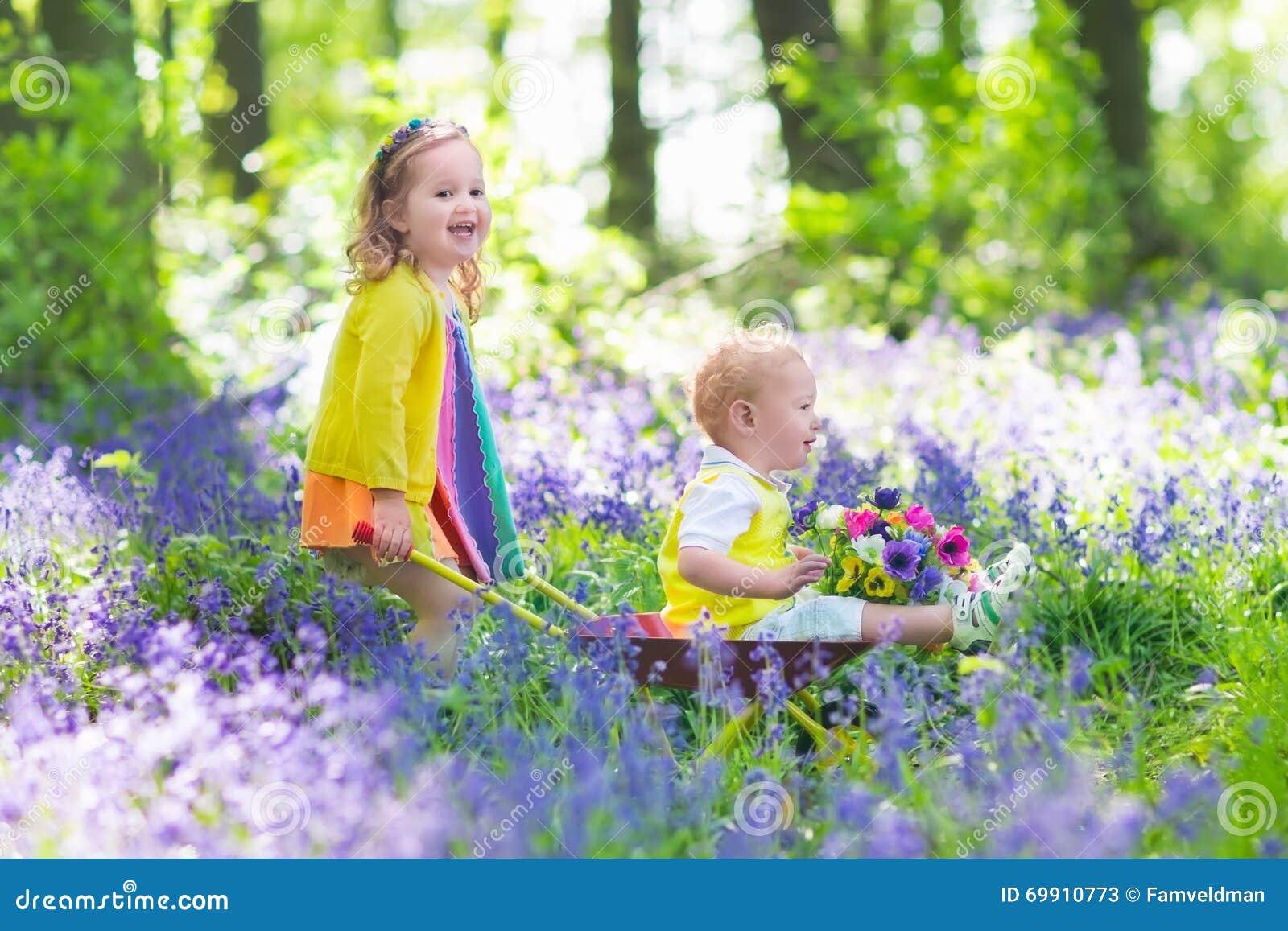 Bambini In Un Giardino Con I Fiori Di Campanula Fotografia