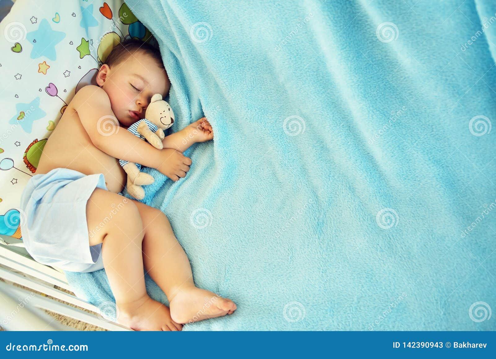 Bambino addormentato con un orso molle del giocattolo ragazzino che si trova in greppia su una coperta blu