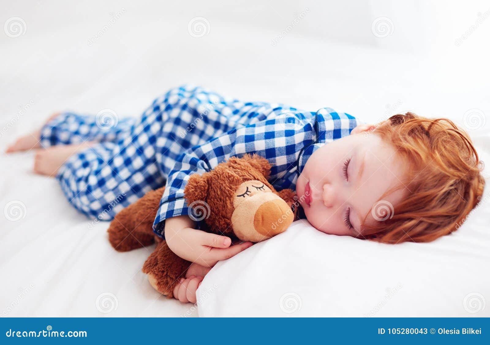 Bambino adorabile del bambino della testarossa che dorme con il giocattolo della peluche in pigiami della flanella