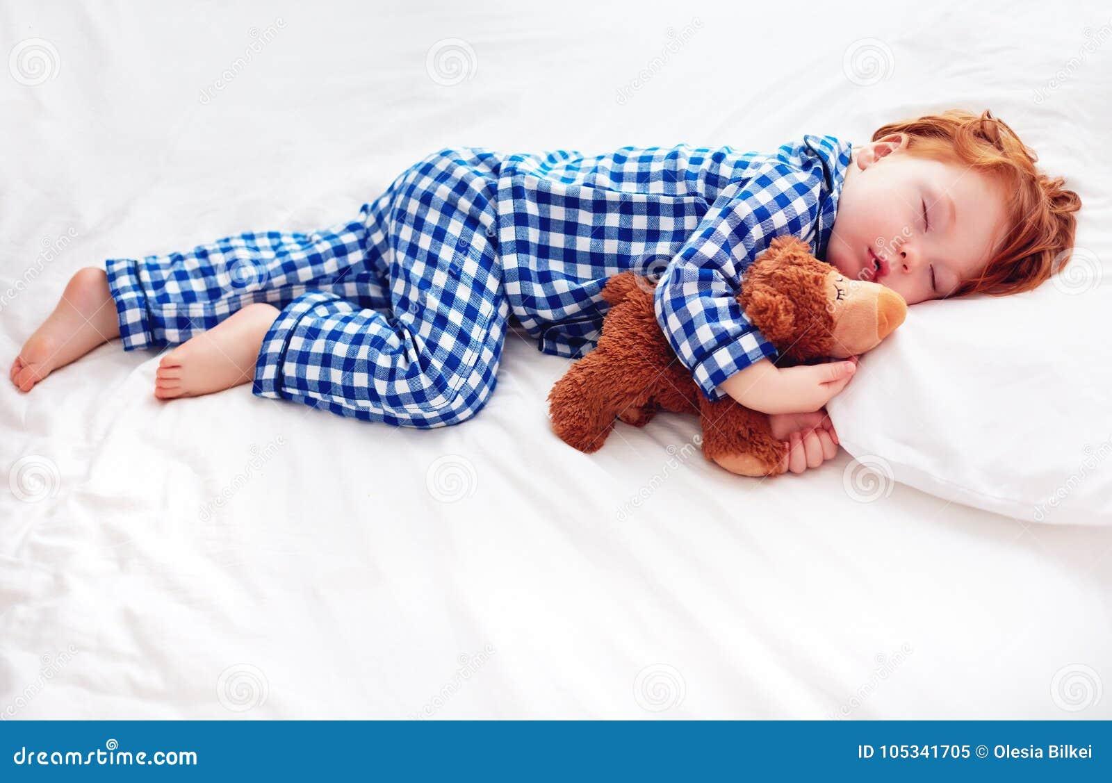 Bambino adorabile del bambino della testarossa in pigiami della flanella che dorme con il giocattolo dello scaldino della peluche