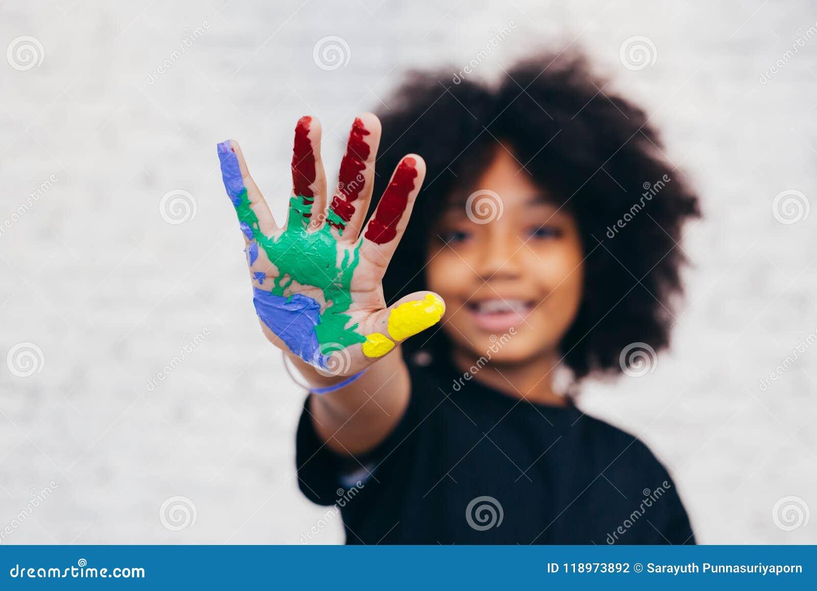 Bambino allegro e creativo afroamericano che ottiene a mani i wi sporchi