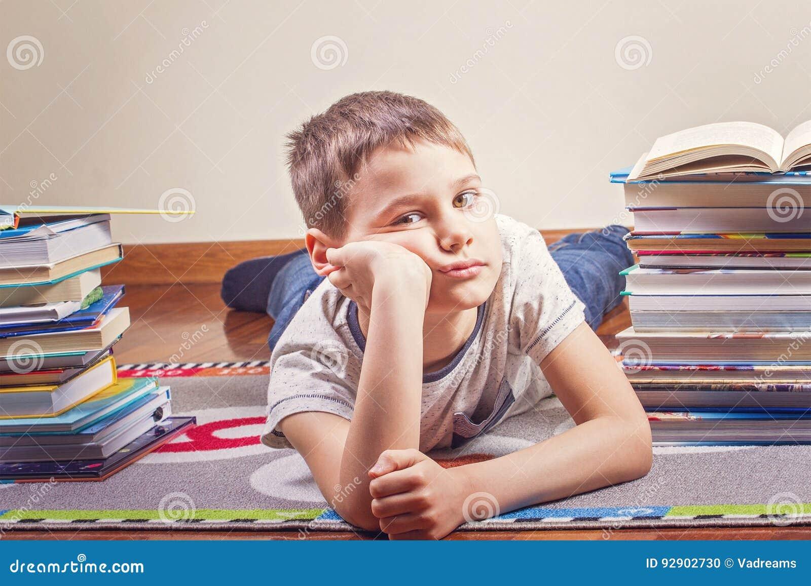 Bambino annoiato che si trova fra i mucchi dei libri