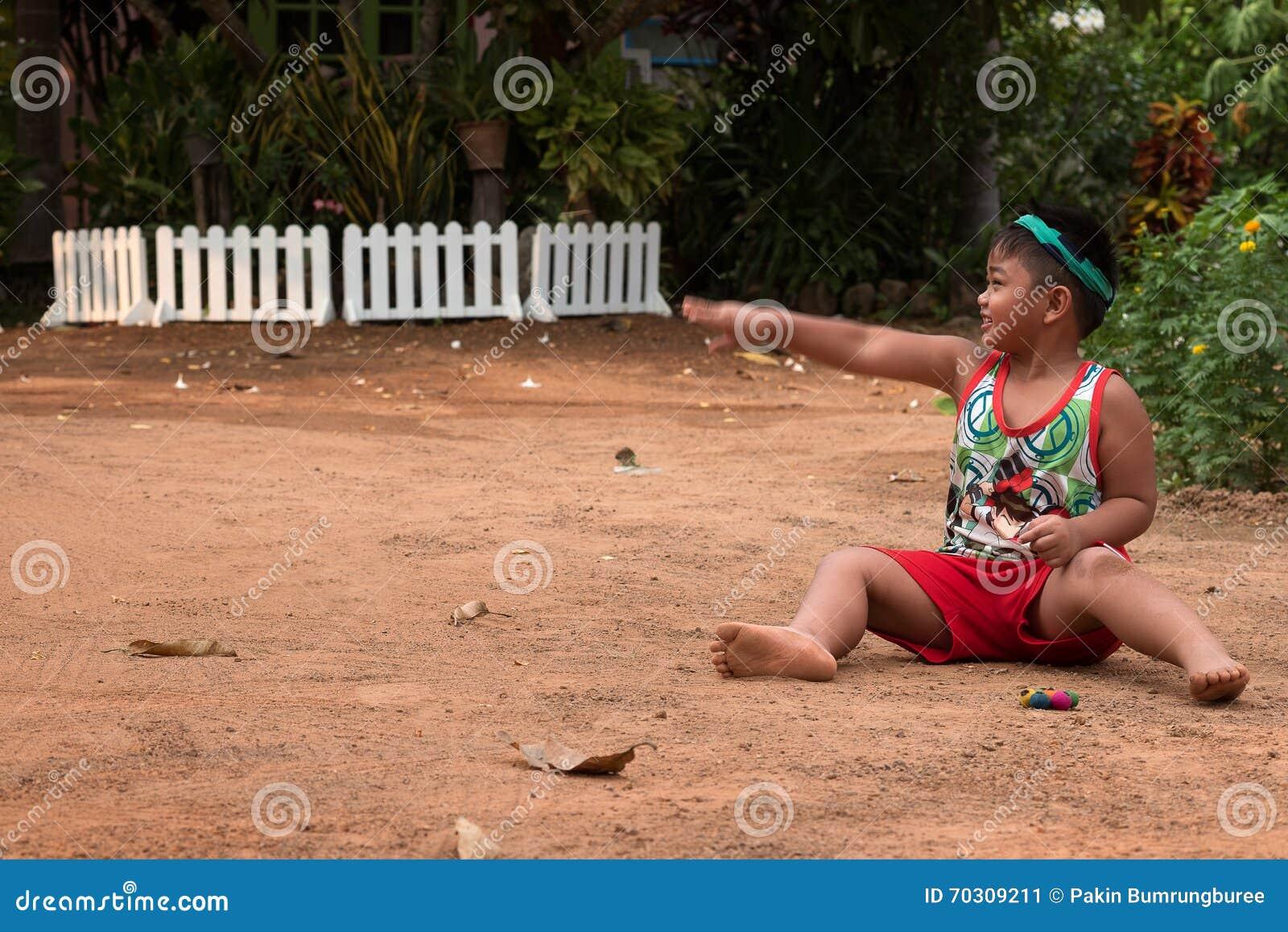 Bambino asiatico che gioca con la sabbia e la palla nel campo da giuoco