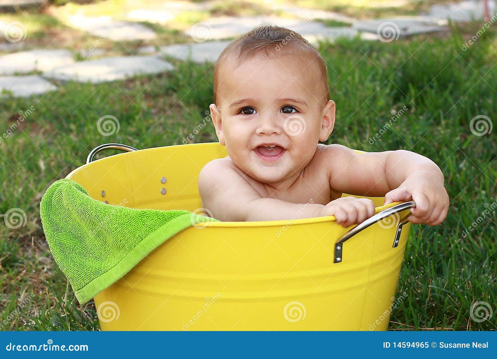 Bambino in benna gialla in giardino
