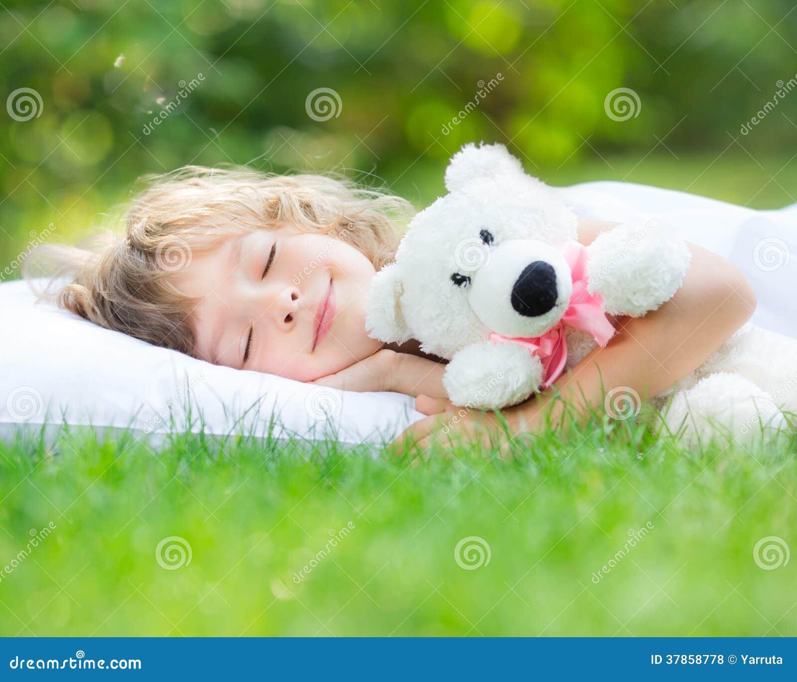 Bambino che dorme nel giardino di primavera