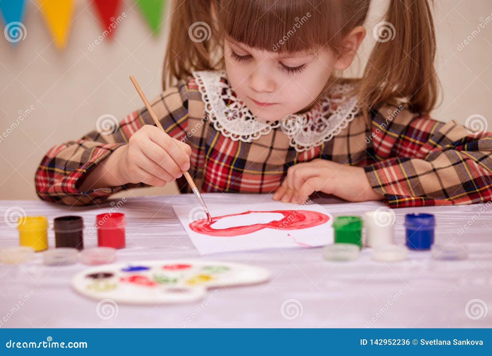 Bambino che fa la cartolina d auguri casalinga La bambina dipinge il cuore sulla cartolina d auguri casalinga come regalo per il