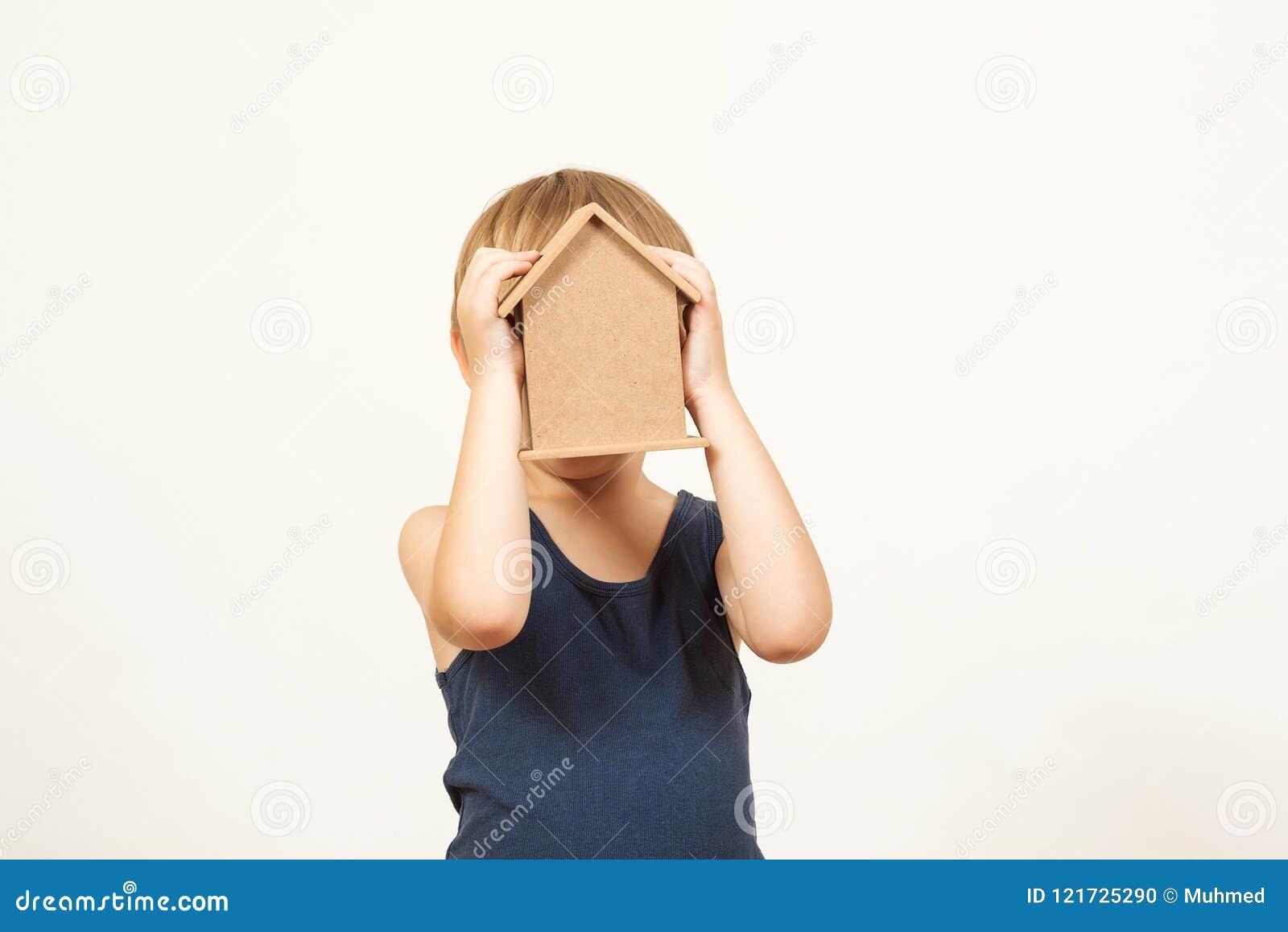 Bambino che gioca con la casa dei giocattoli Il piccolo bambino ha nascosto il suo fronte dietro una casetta Casetta della tenuta