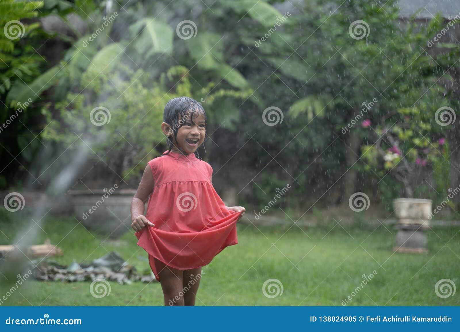 Bambino che gode del gioco con la spruzzata dell acqua in giardino