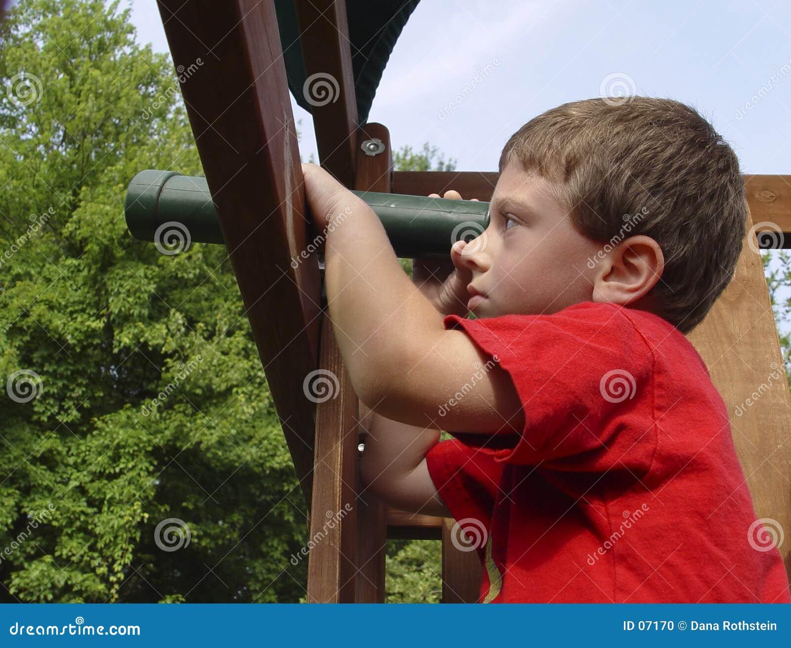 Bambino che per mezzo del telescopio