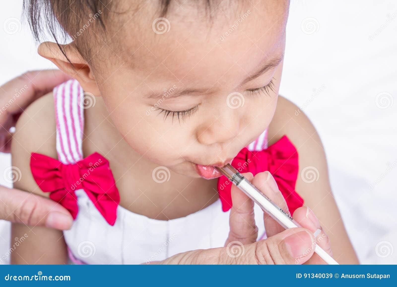 Bambino che si alimenta con la medicina liquida con una siringa