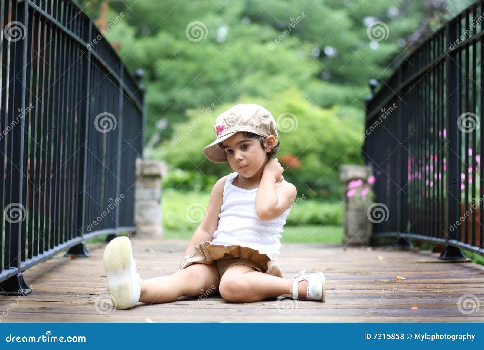 Bambino che si siede sul ponticello
