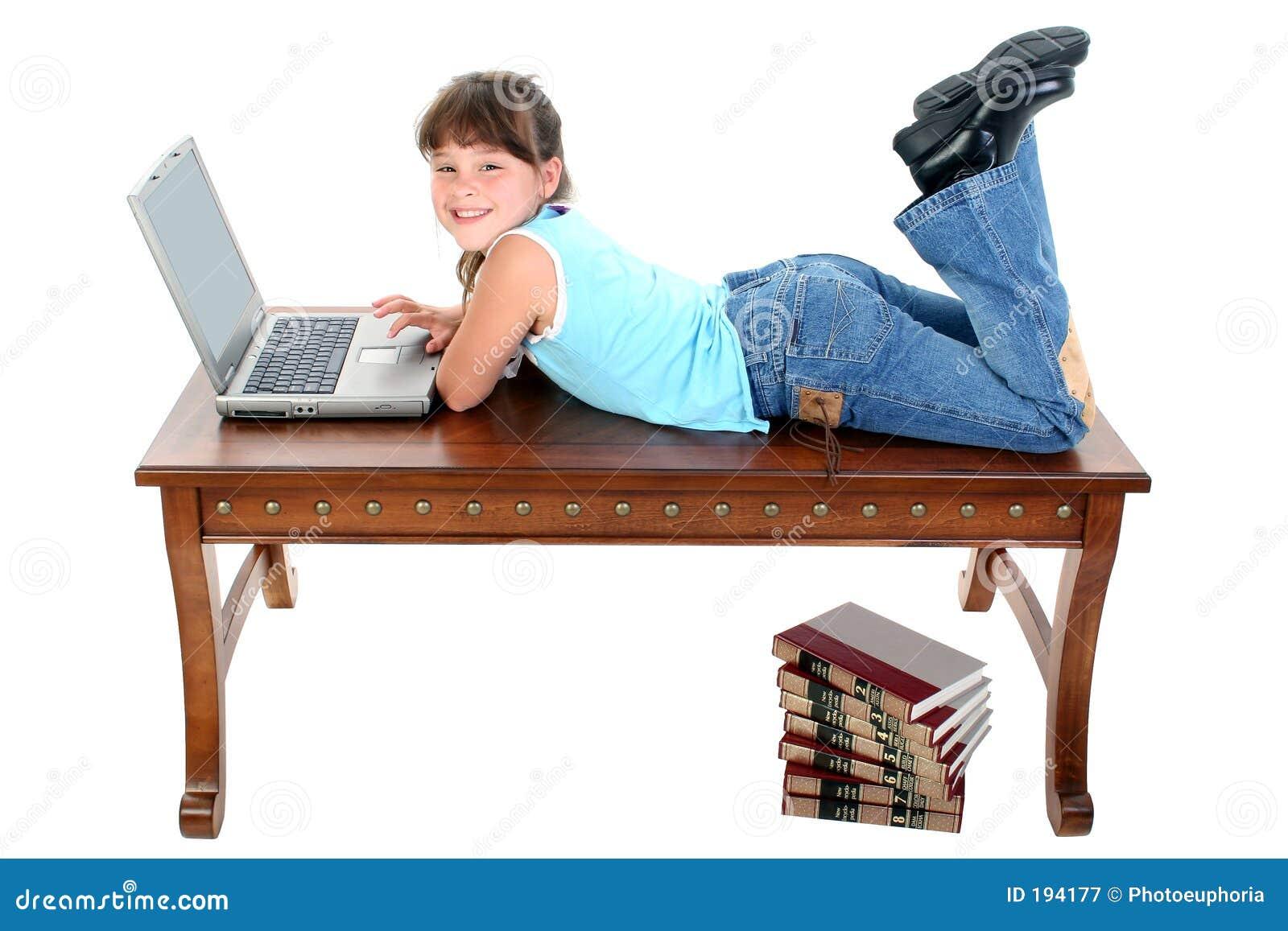Bambino che si siede sulla Tabella che lavora al computer portatile