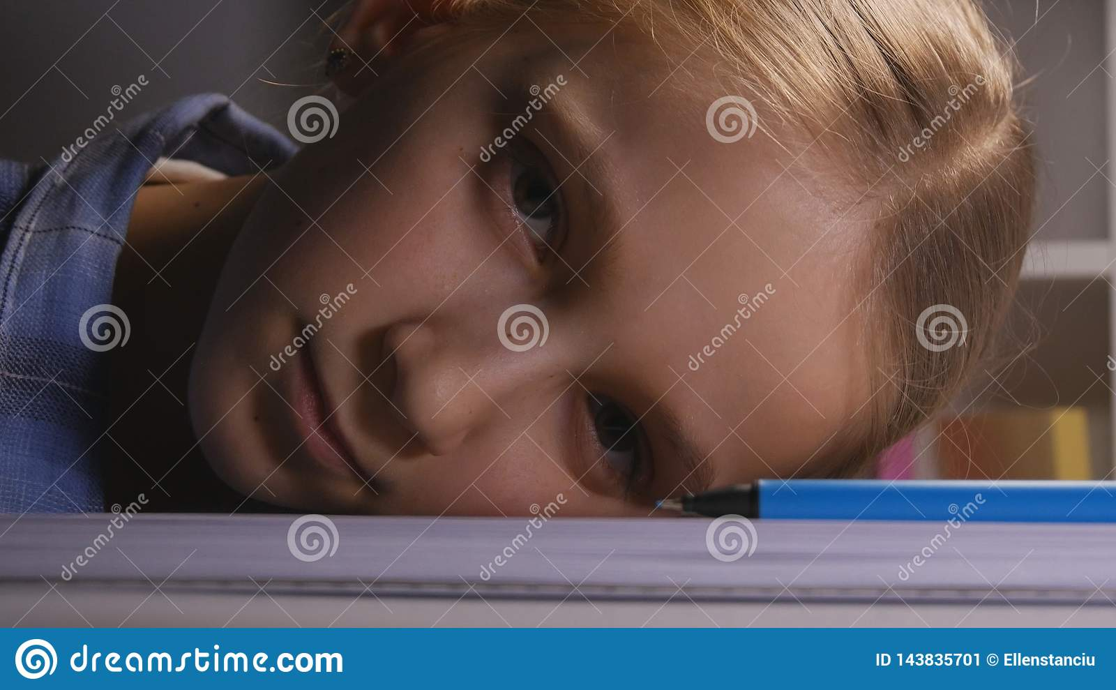Bambino che studia nella notte, scrittura annoiata del bambino nello studente triste scuro e stanco Learning