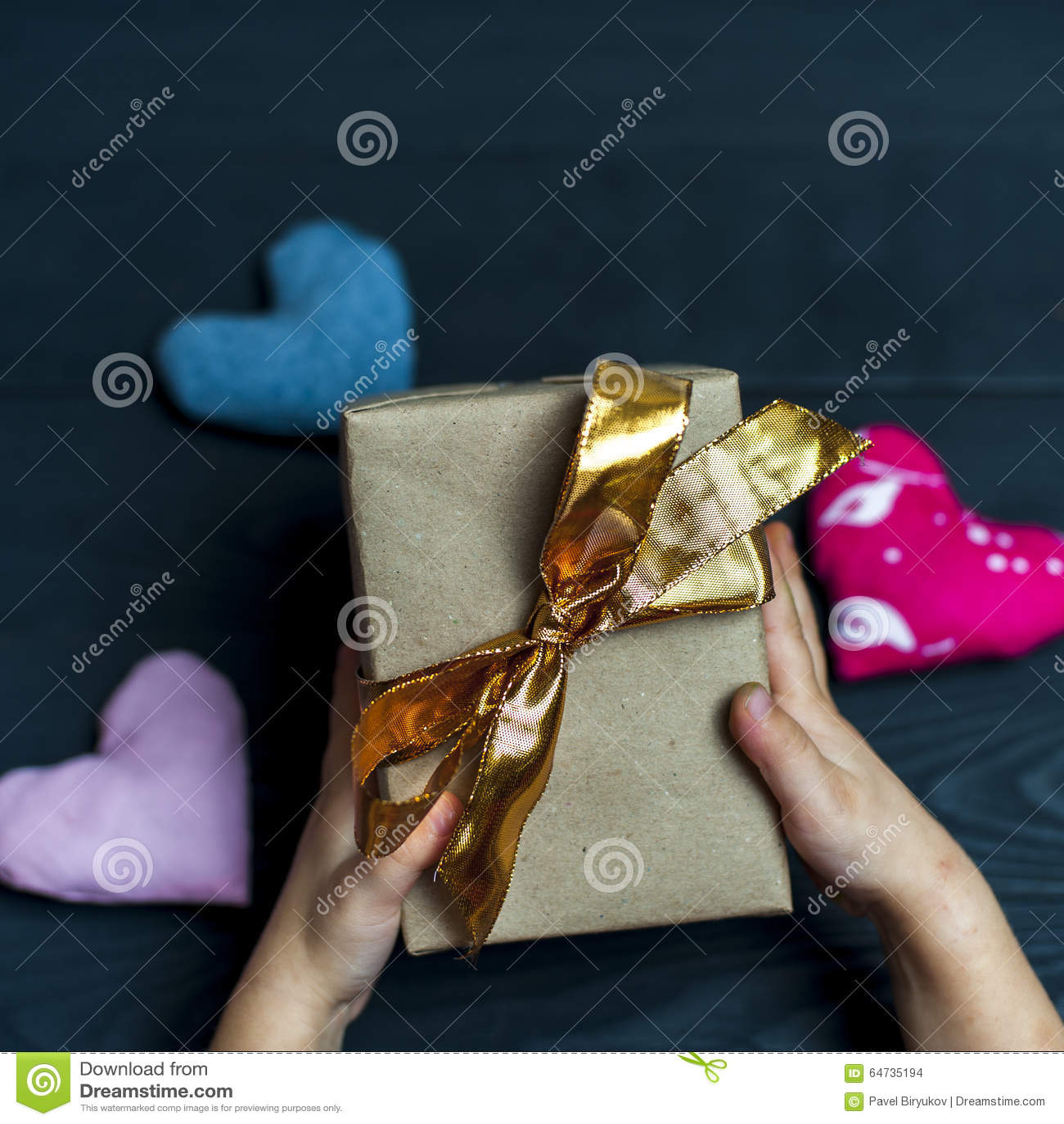 Bambino che tiene un contenitore di regalo con il nastro dorato