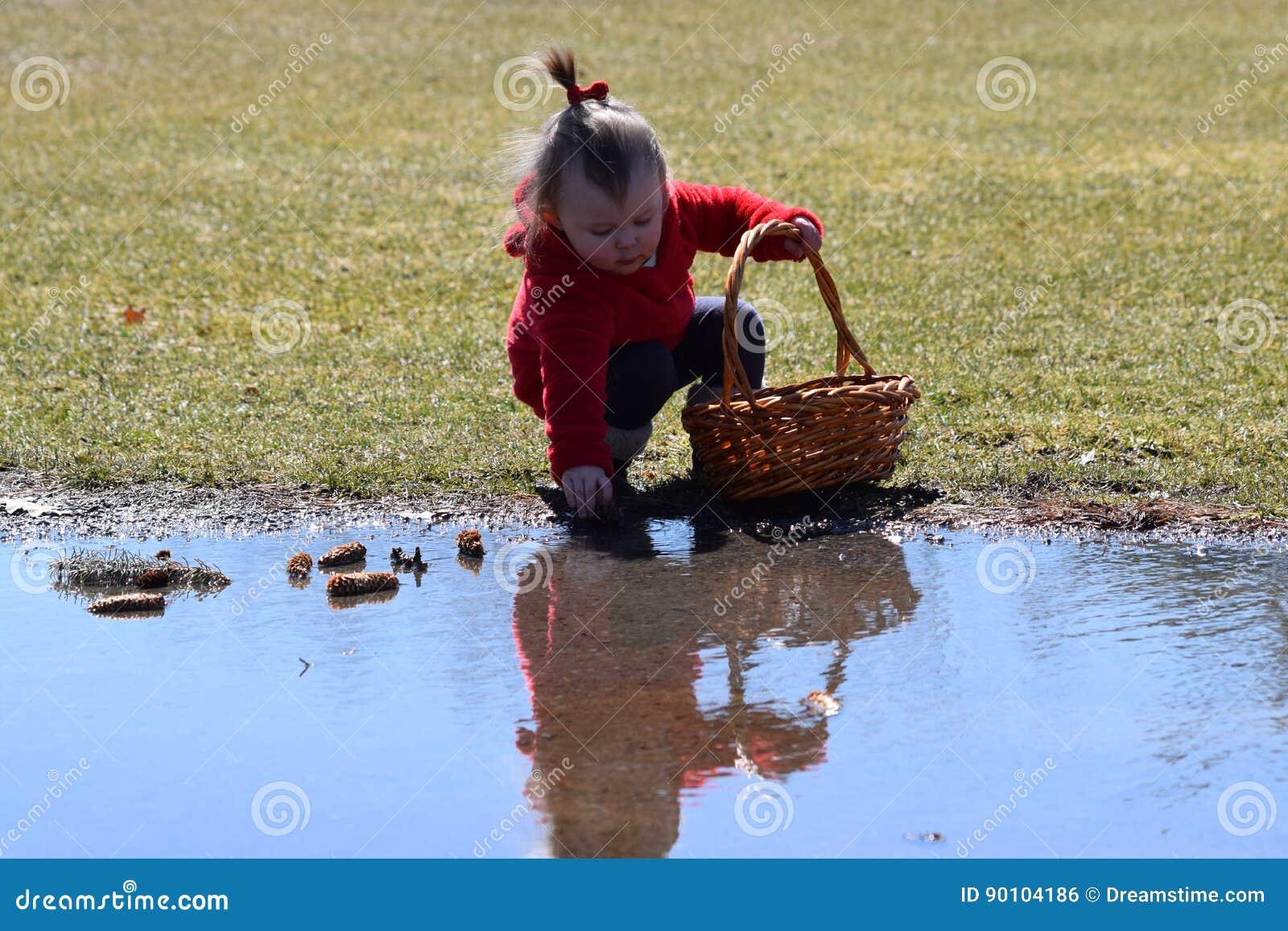 Bambino con il cappotto rosso che si inginocchia alla riflessione dell acqua
