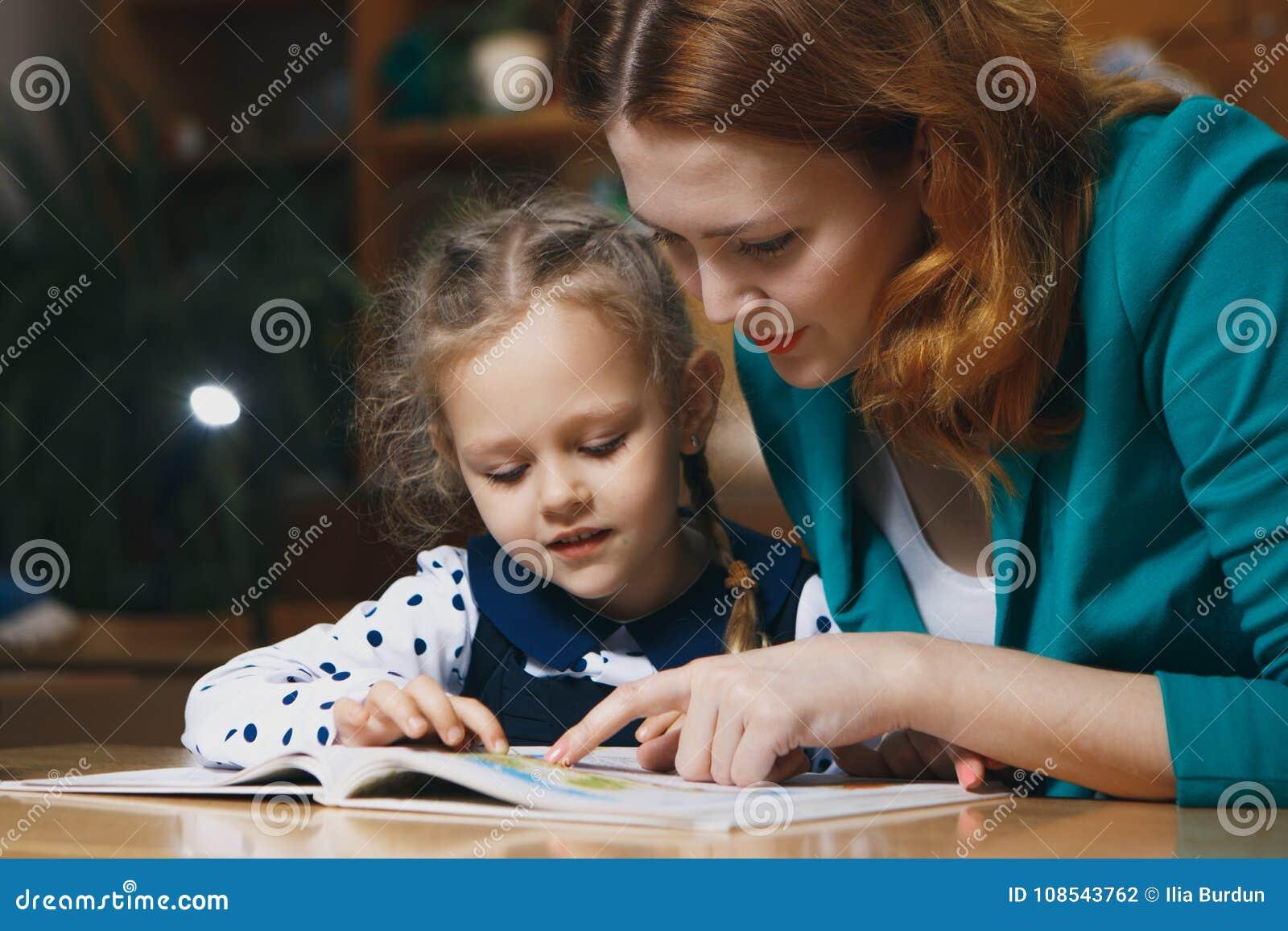 Bambino d aiuto della madre dopo la scuola bambino in età prescolare che fa compito con aiuto dell istitutore concetto d istruzio