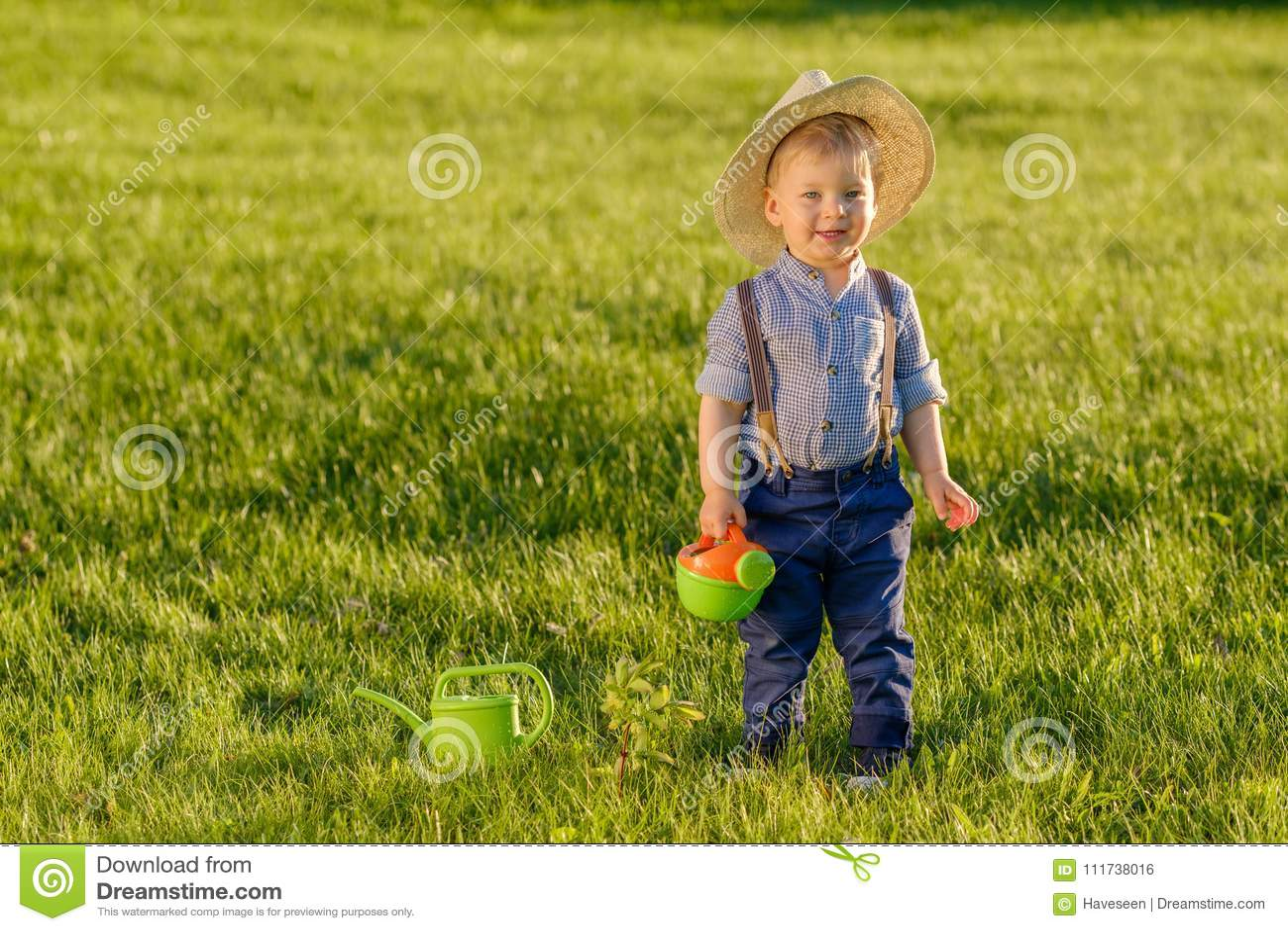 Bambino del bambino all aperto Cappello di paglia d uso del neonato di un anno facendo uso dell annaffiatoio