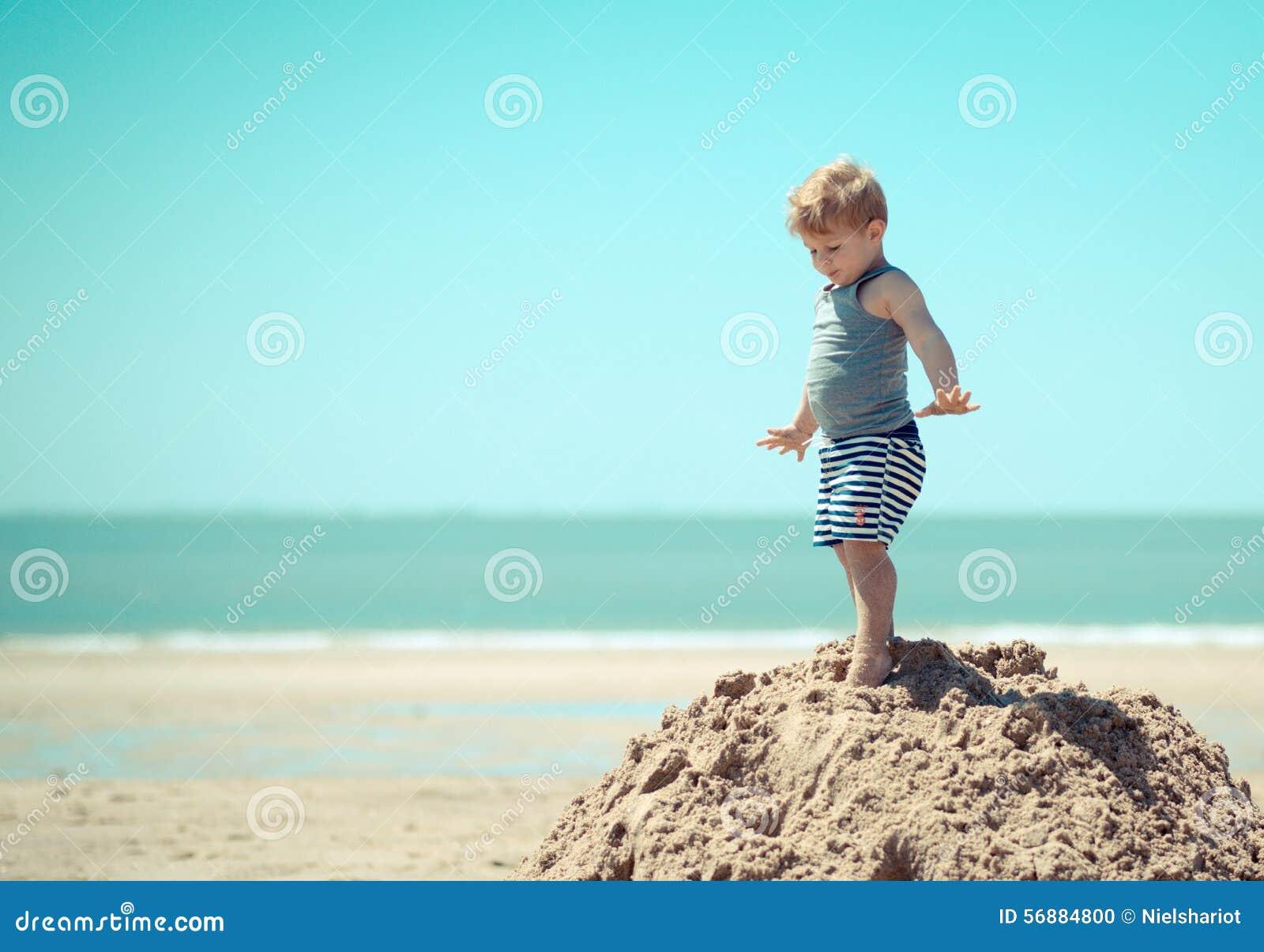Bambino del ragazzino che sta davanti ad una scogliera
