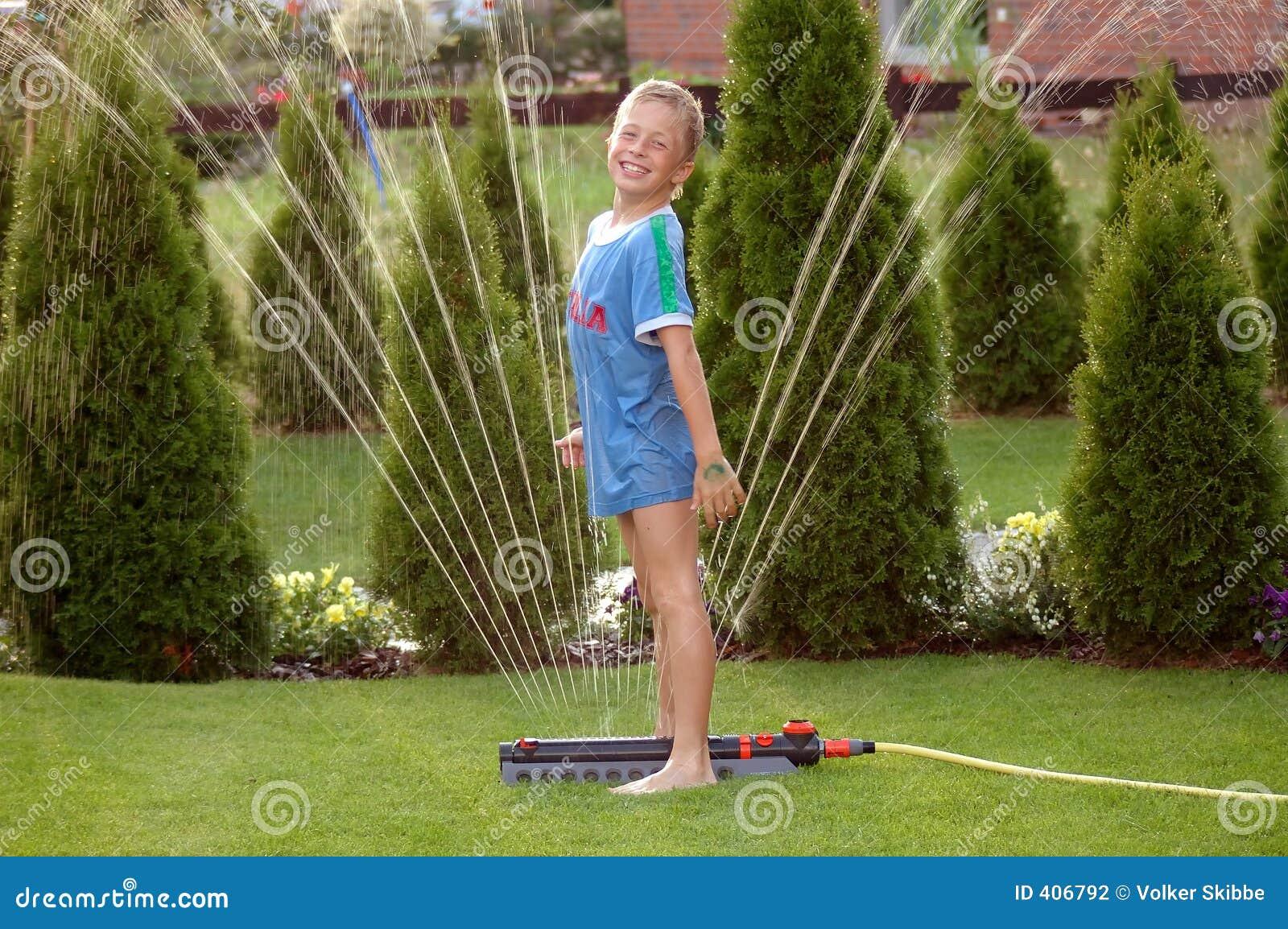 Bambino del ragazzo e spruzzatore 2 del giardino