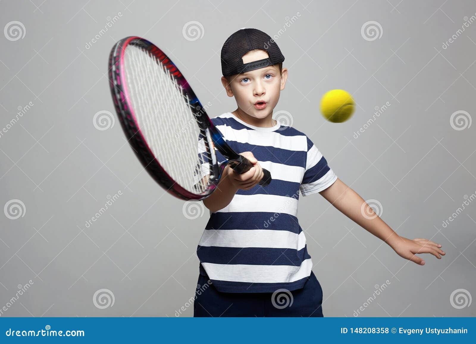 Bambino di sport Bambino con la racchetta e la palla di tennis