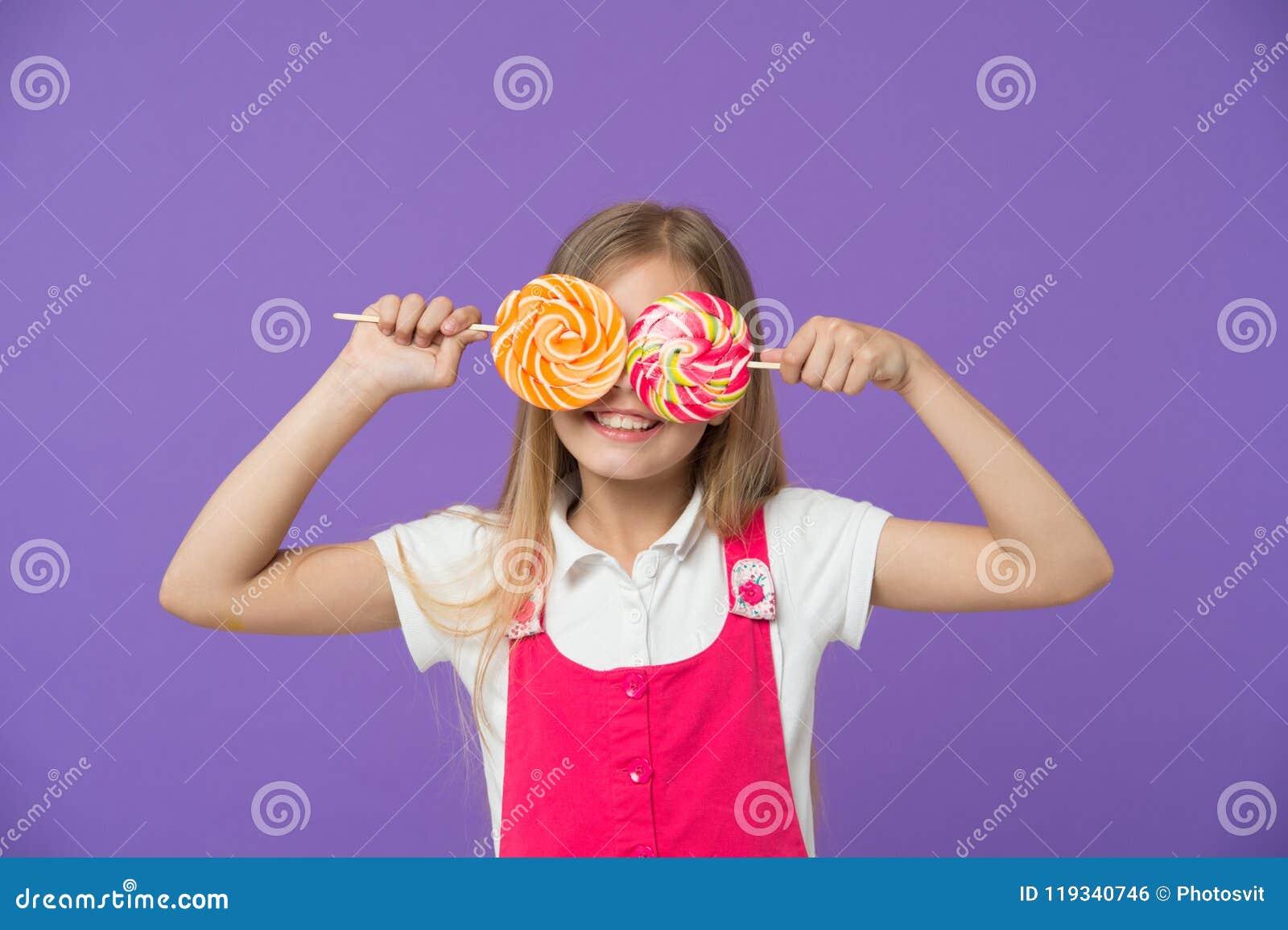 Bambino divertente con le lecca-lecca su fondo viola Ragazza che sorride con gli occhi della caramella Sorriso del bambino con le