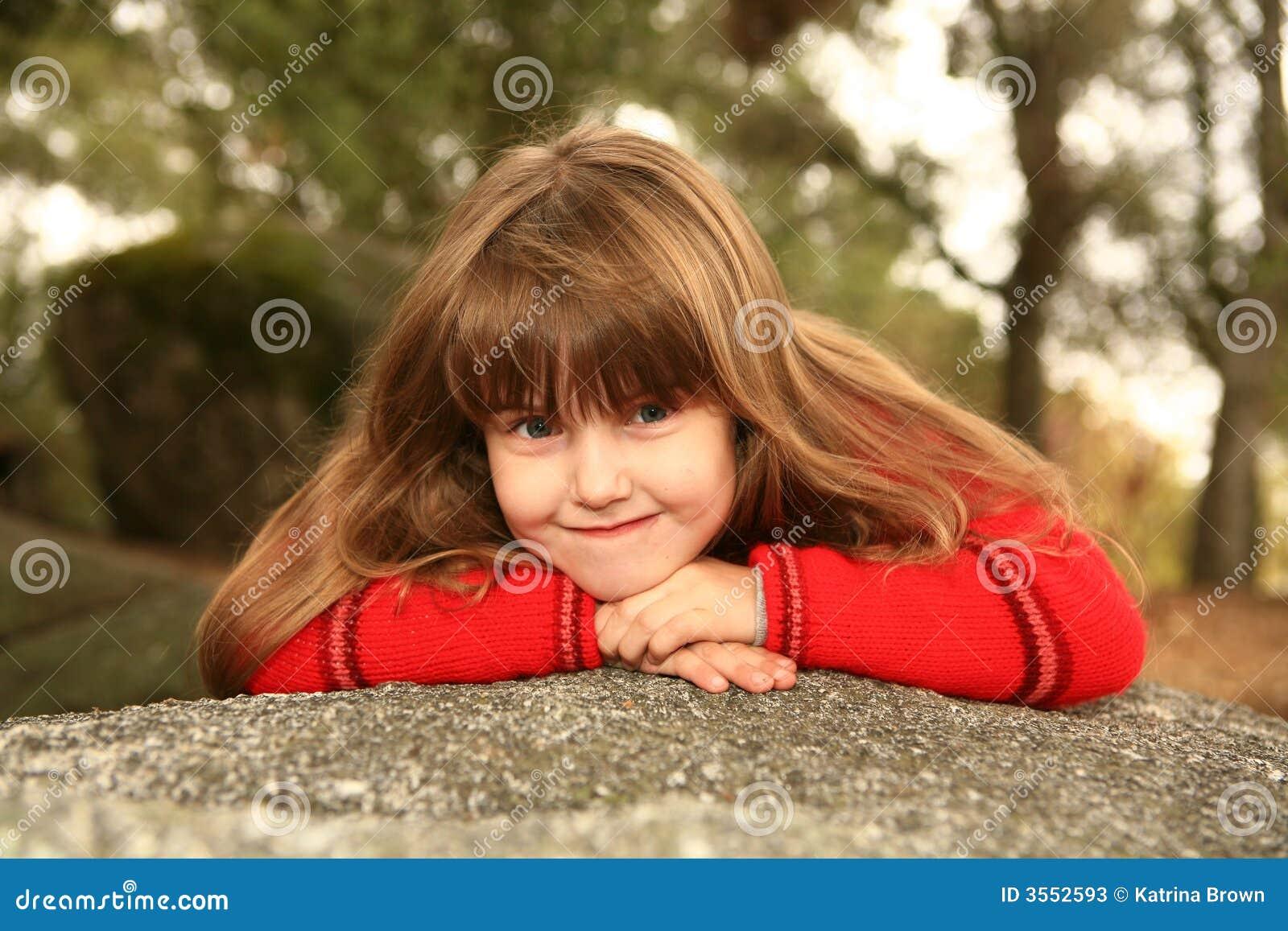 Bambino dolce timido all aperto su una roccia