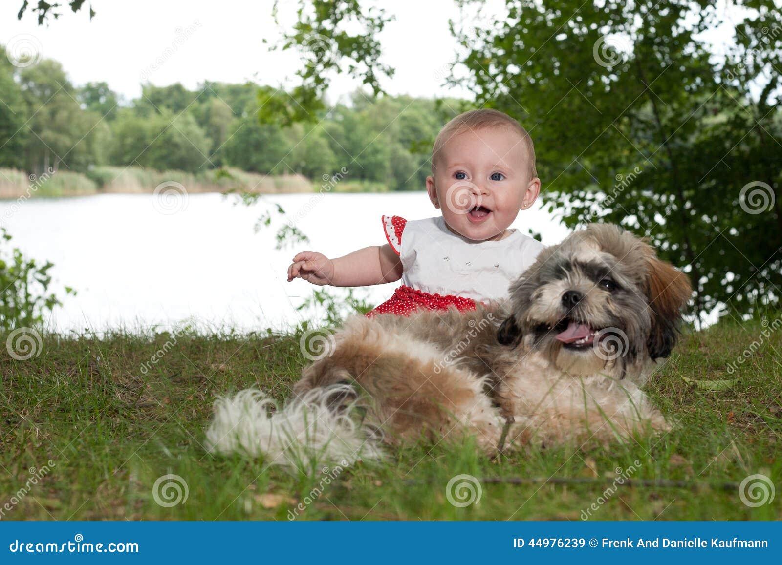 Bambino e cucciolo felici vicino al lago